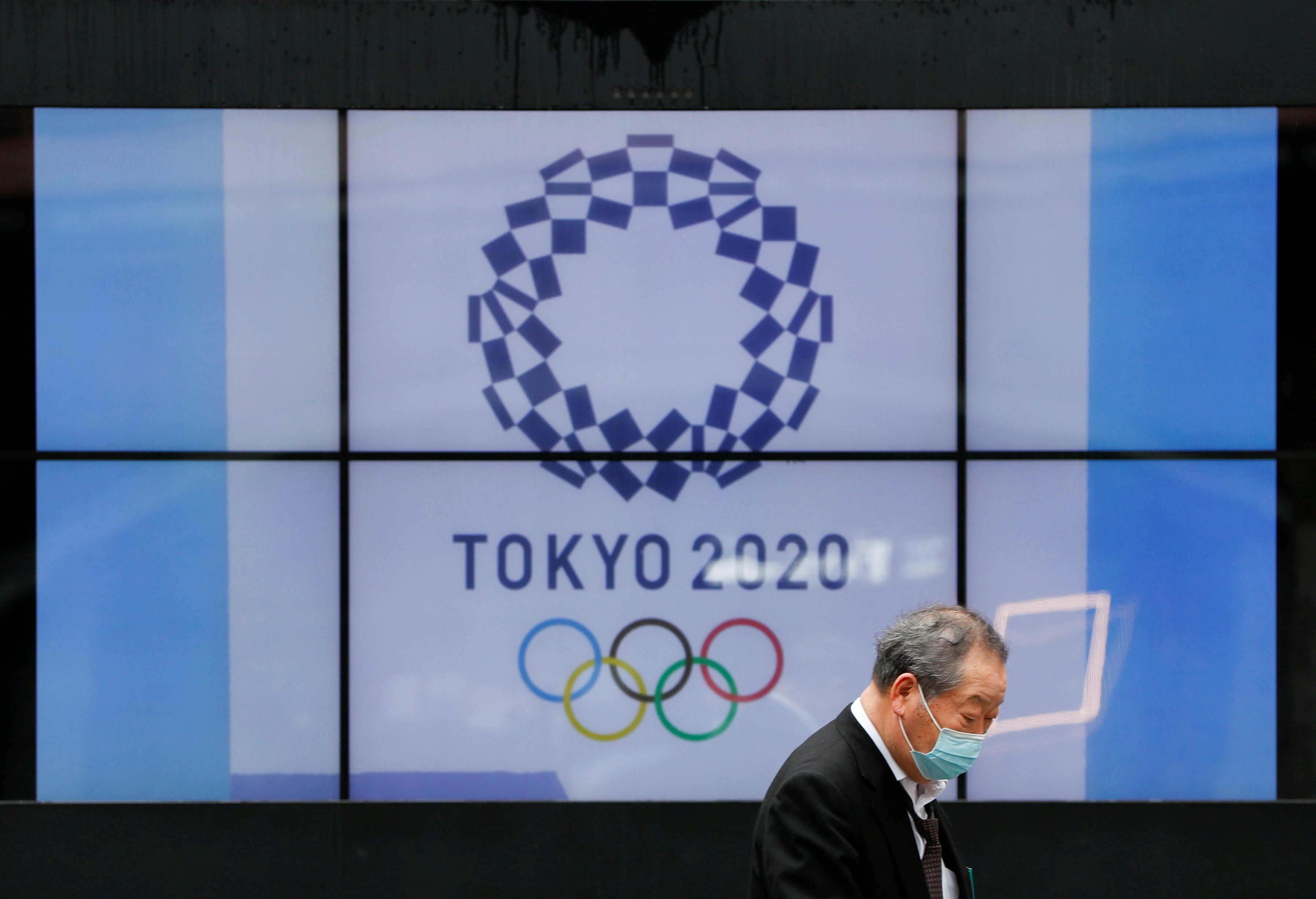 A passerby wearing a protective face mask walks past a screen showing the logo of the Tokyo 2020 Olympic Games that have been postponed to 2021 due to the coronavirus disease (COVID-19) pandemic, in Tokyo, Japan, April 14, 2021.   REUTERS/Issei Kato/File Photo