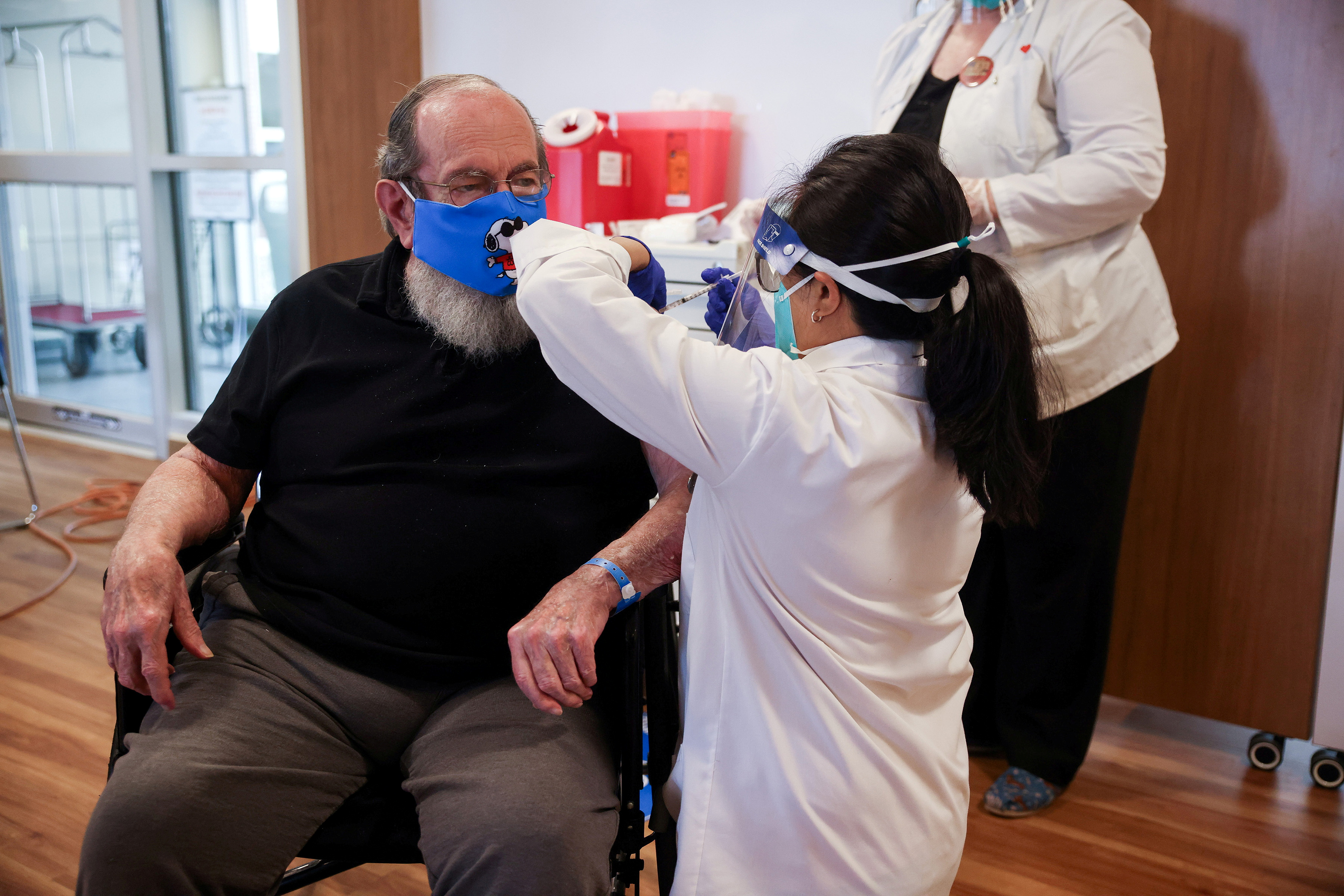 U.S. Air Force veteran Robert Aucoin, 78, receives a coronavirus disease (COVID-19) vaccine dose at the Soldiers' Home in Holyoke, Massachusetts, U.S. December 29, 2020. Hoang 'Leon' Nguyen/The Republican/Pool via REUTERS