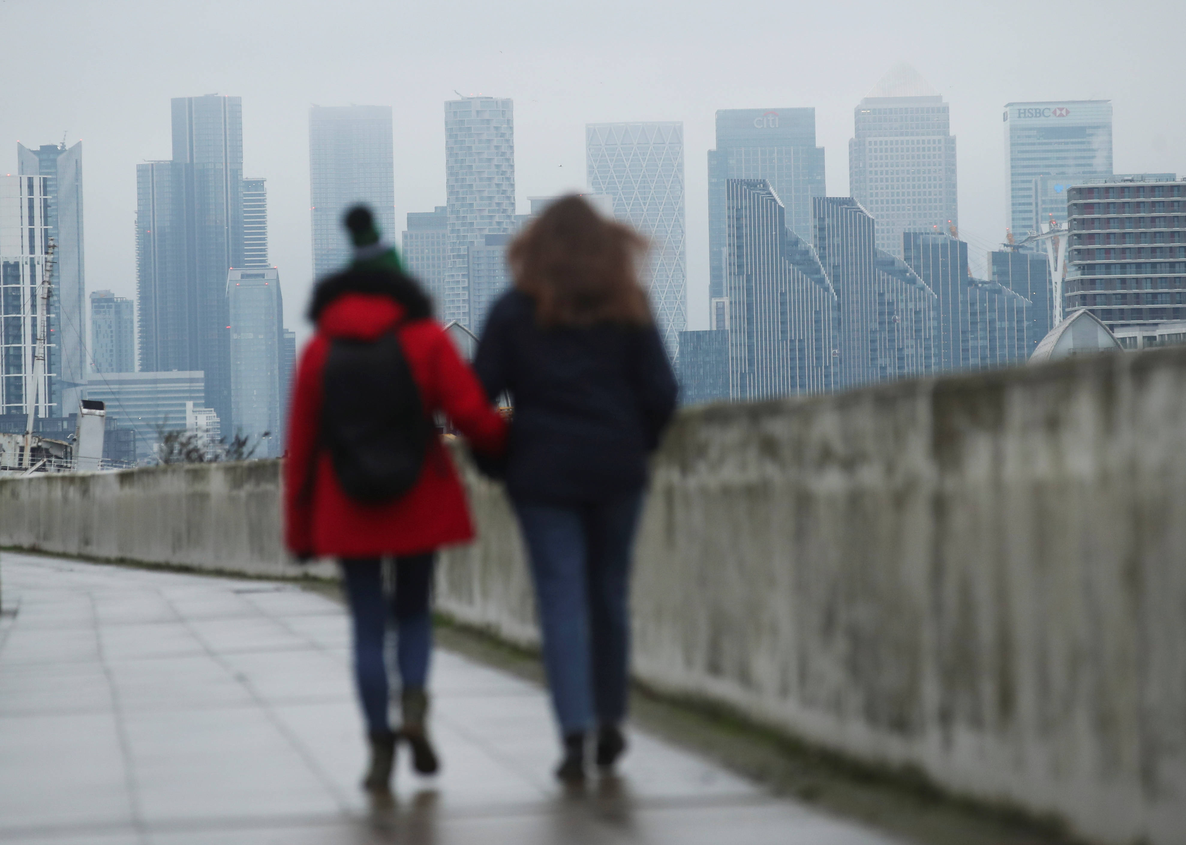 Buildings are seen in the Canary Wharf business district, as people walk along a footpath, amid the outbreak of the coronavirus disease (COVID-19), in London, Britain January 27, 2021. REUTERS/Peter Cziborra