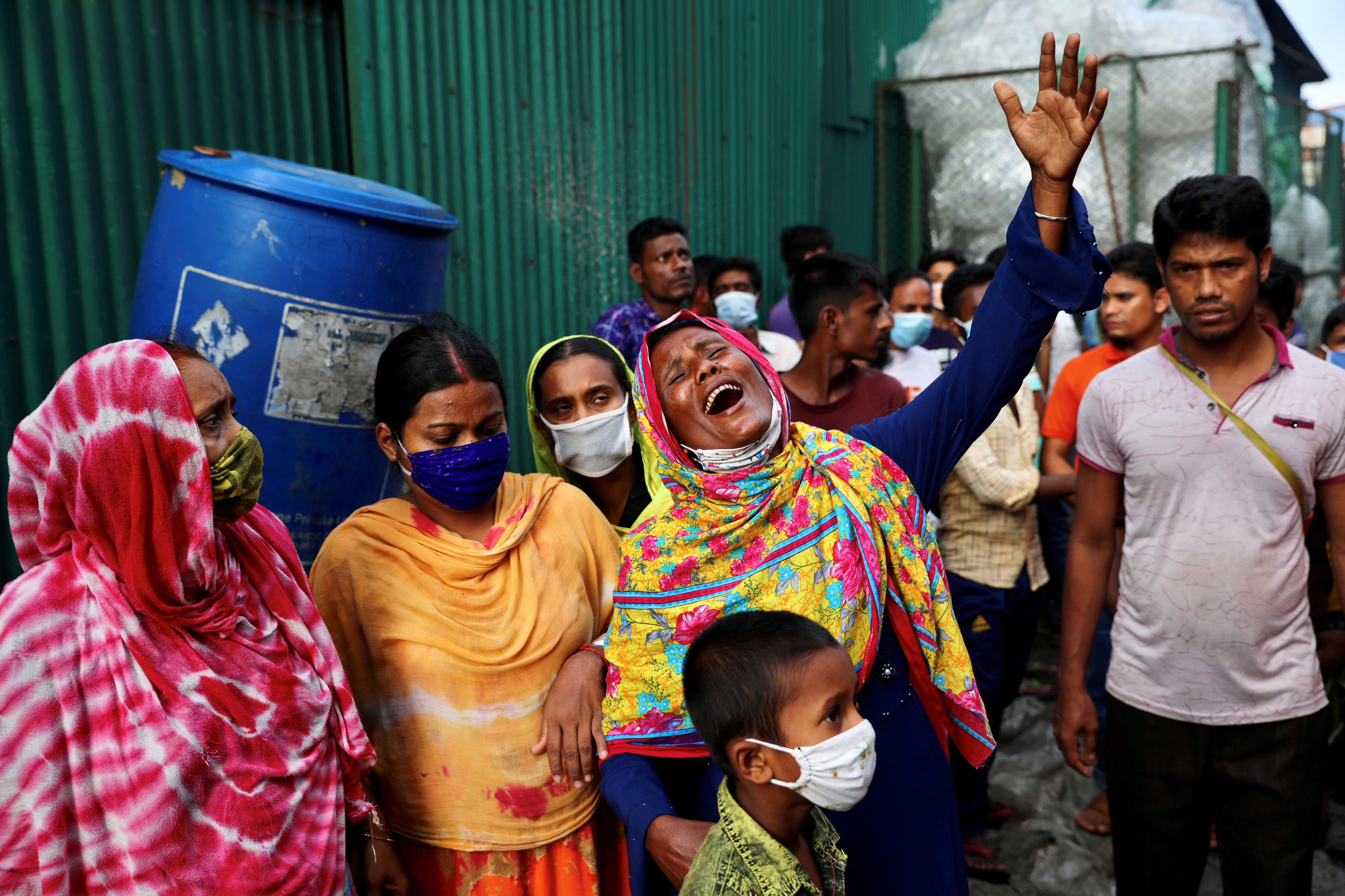 Unidentified relatives of the victims mourn at the site after a fire broke out at a factory named Hashem Foods Ltd. in Rupganj of Narayanganj district, on the outskirts of Dhaka, Bangladesh, July 9, 2021. REUTERS/Mohammad Ponir Hossain