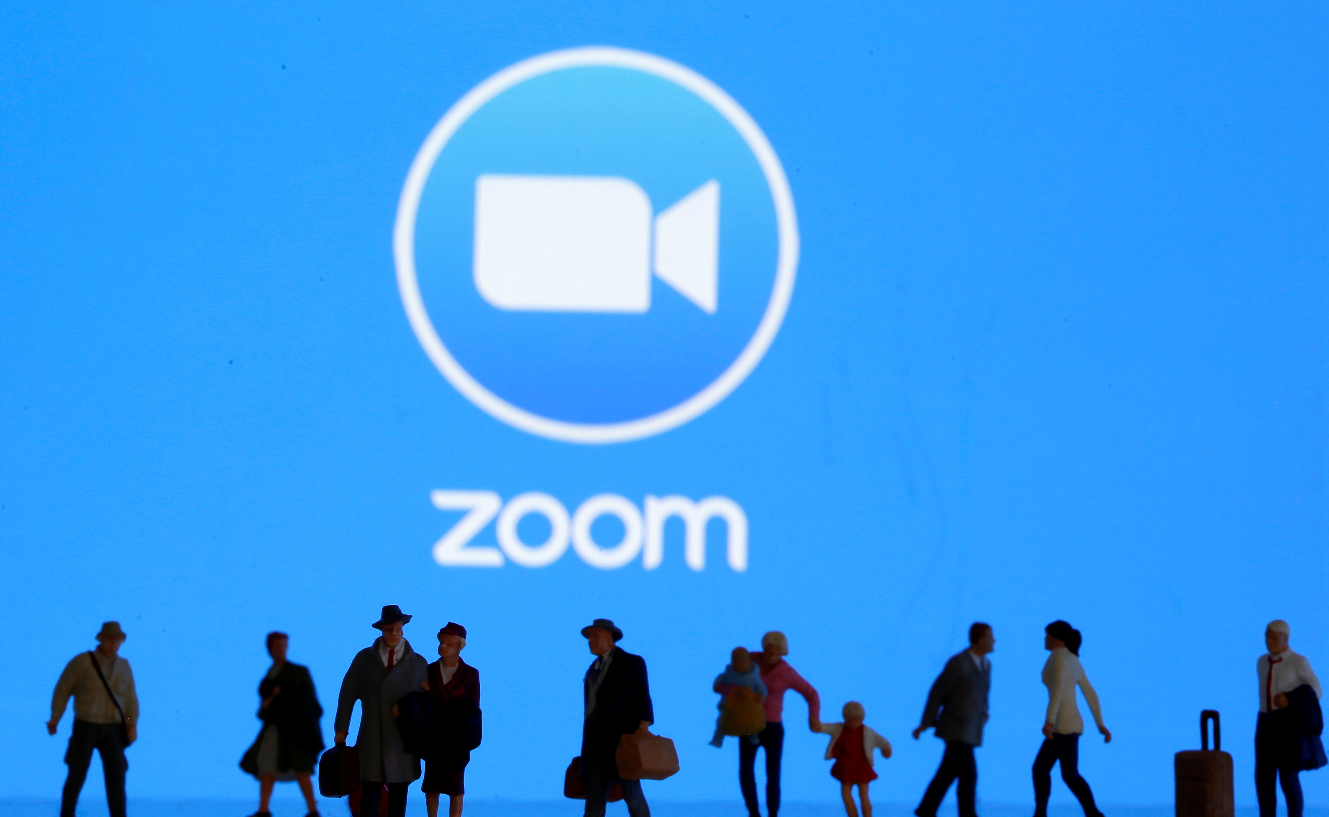 Small toy figures are seen in front of diplayed Zoom logo in this illustration taken March 19, 2020. REUTERS/Dado Ruvic/Illustration