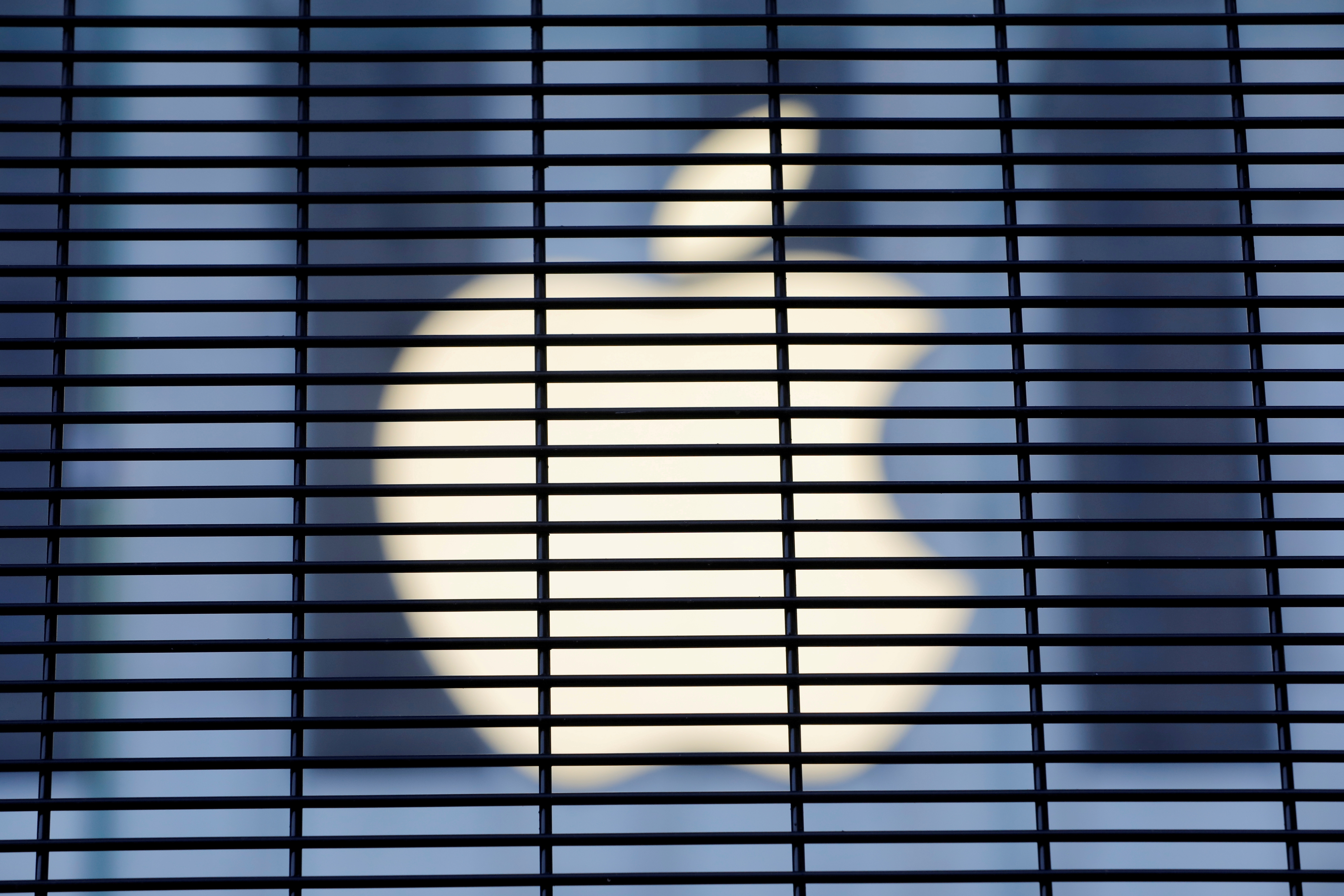 The Apple logo is seen through a security fence erected around the Apple Fifth Avenue store as votes continue to be counted following the 2020 U.S. presidential election, in Manhattan, New York City, U.S., November 5, 2020. REUTERS/Andrew Kelly/File Photo