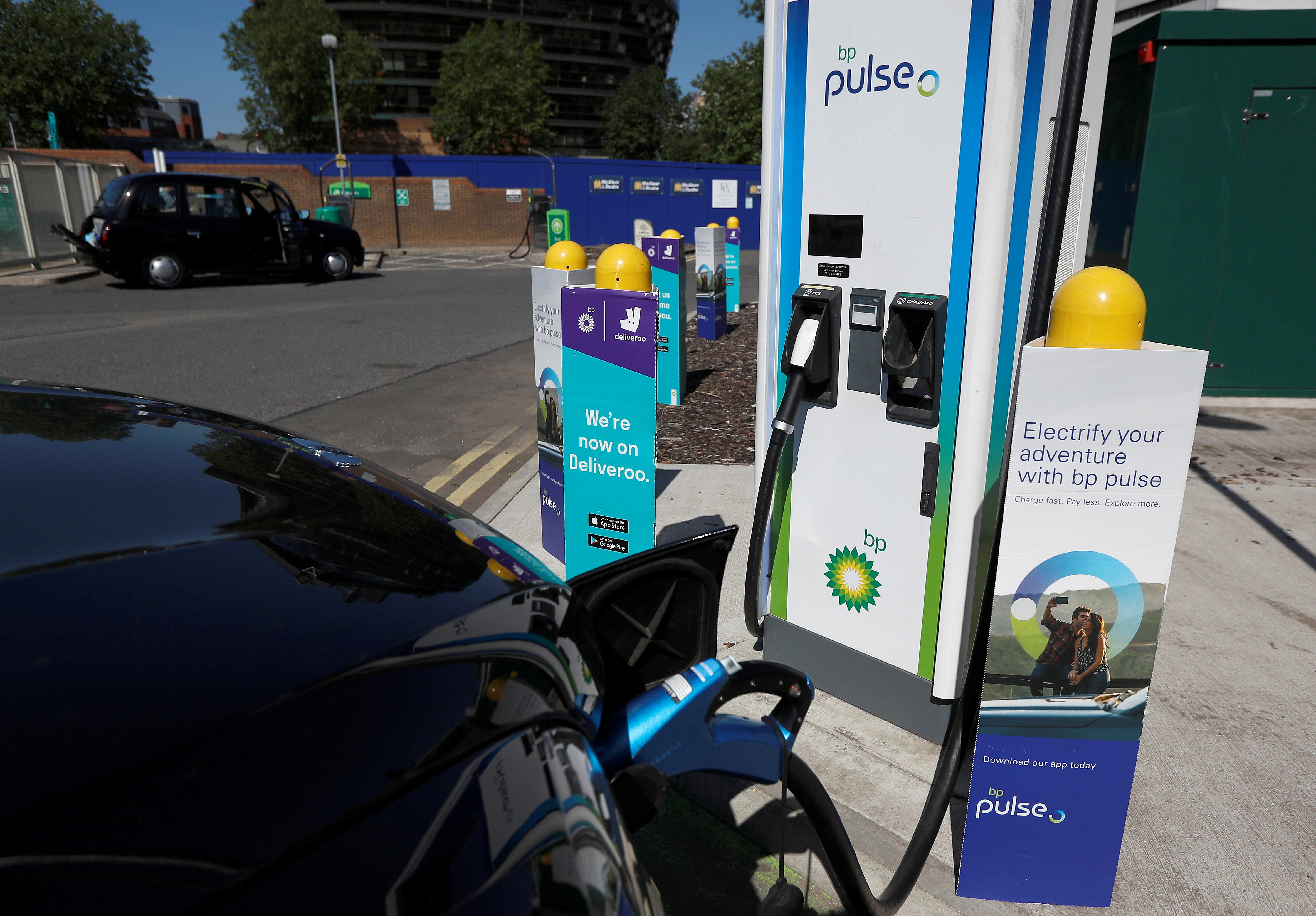An electric powered taxi is seen being charged at a BP Pulse electric vehicle charging point in London, Britain, July 16, 2021. Picture taken July 16, 2021.  REUTERS/Peter Nicholls
