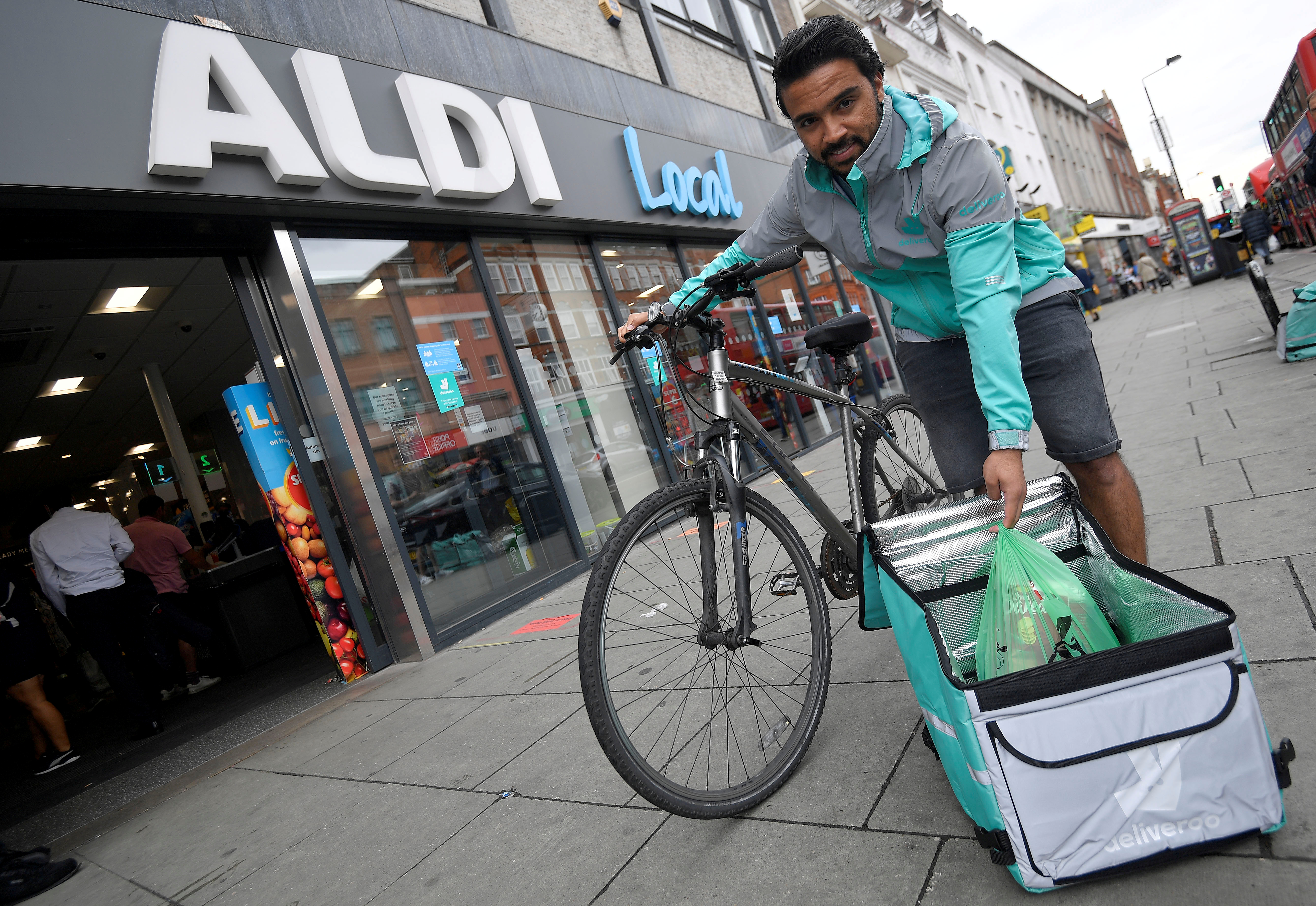 Abdelaziz Abdou, a Deliveroo delivery rider, poses with a bag of Aldi groceries, as discount supermarket chains Aldi and Lidl look poised to accelerate their push into home delivery to satisfy burgeoning demand for online grocery shopping in a shift expected to endure beyond the coronavirus crisis, in London, Britain, June 17, 2020.  REUTERS/Toby Melville/File Photo