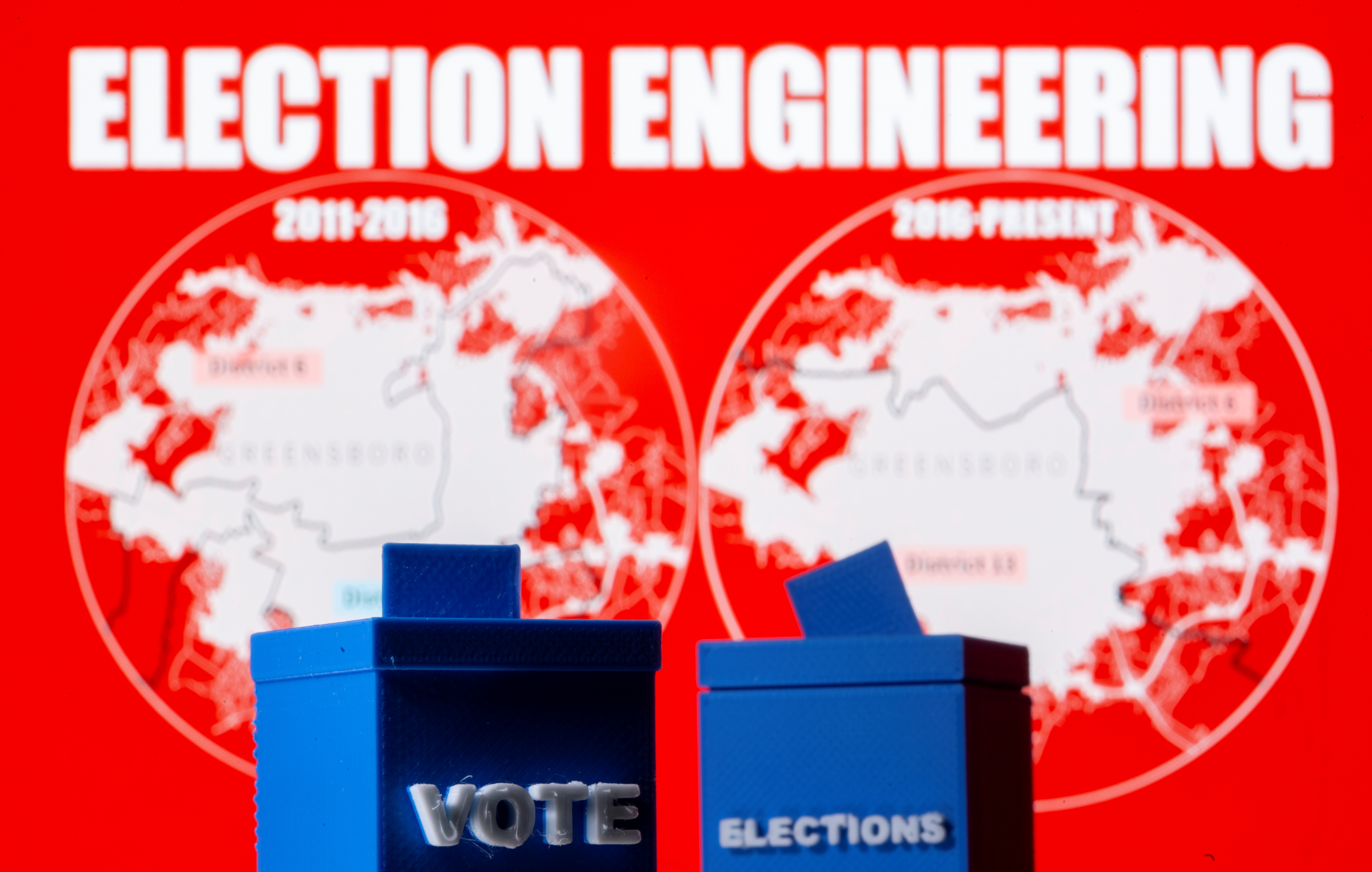 A 3D printed ballot boxes are seen in front of displayed North Carolina district maps in this illustration taken August 13, 2021. REUTERS/Dado Ruvic/Illustration
