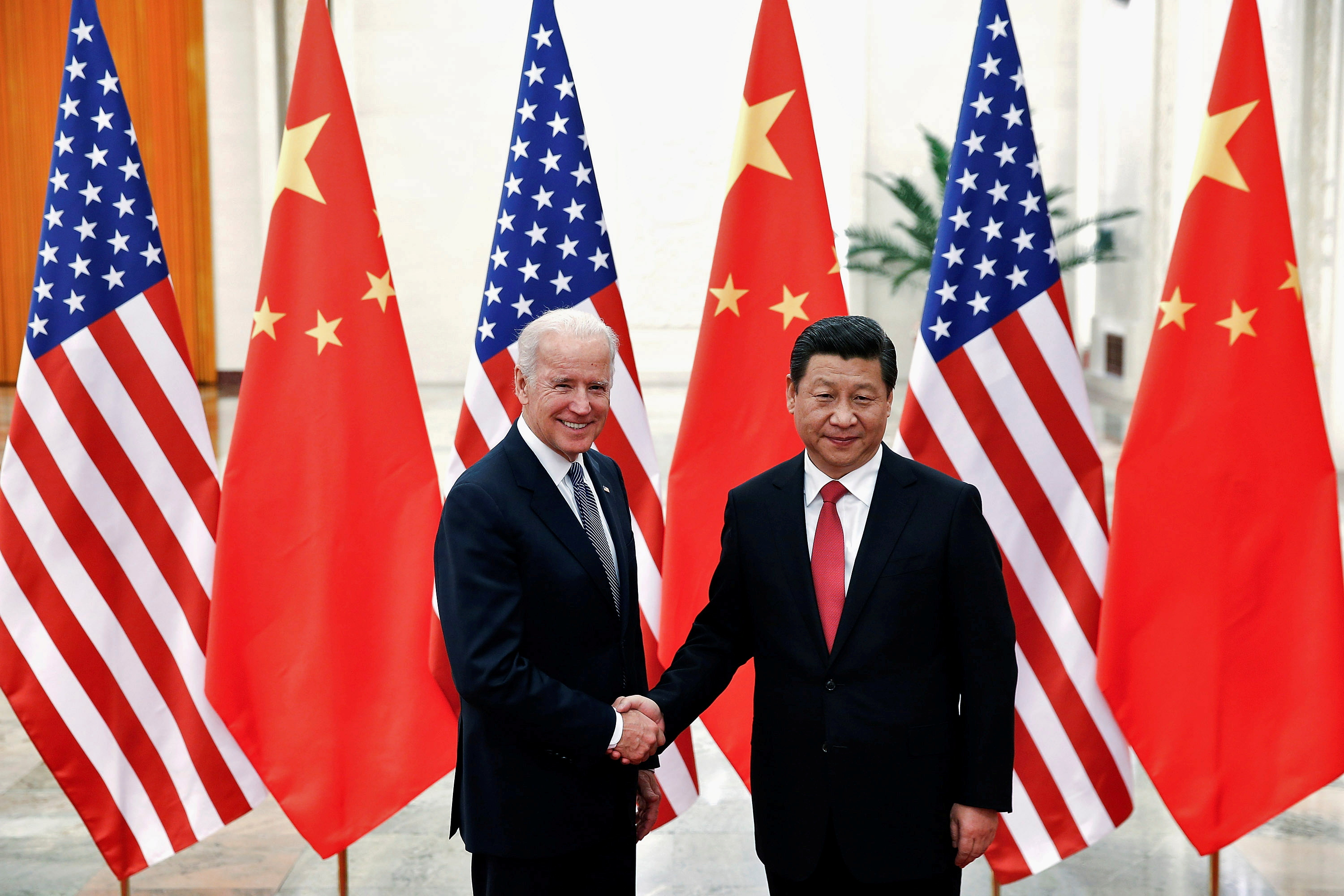 Chinese President Xi Jinping shakes hands with then-U.S. Vice President Joe Biden (L) inside the Great Hall of the People in Beijing December 4, 2013. REUTERS/Lintao Zhang/Pool/File Photo