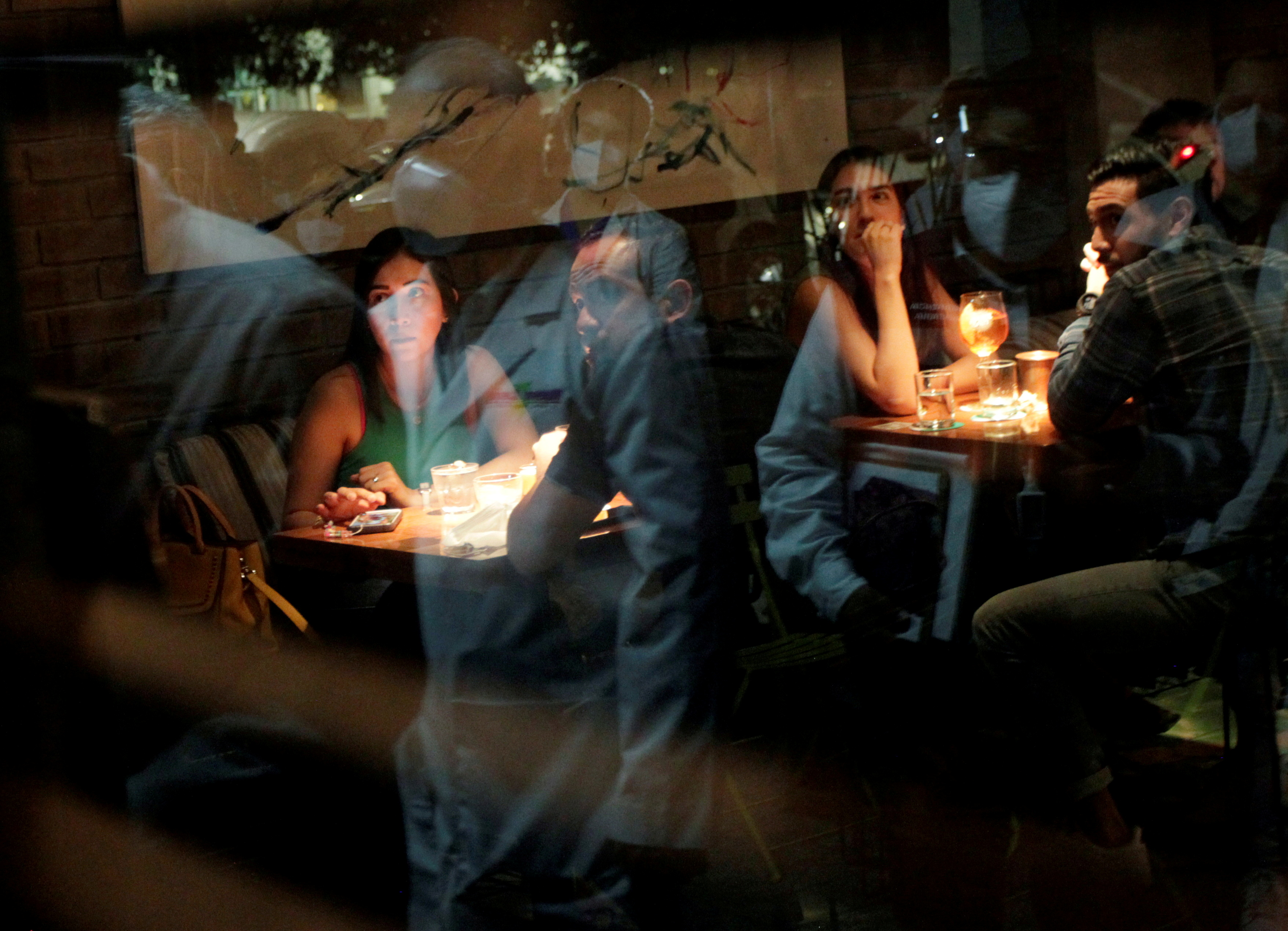 Medical workers are reflected on a window during a tour in nightclubs and restaurants to check that they do not exceed the allowed capacity, amid the coronavirus disease (COVID-19) outbreak, in San Pedro Garza Garcia, on the outskirts of Monterrey, Mexico July 24, 2021. Picture taken July 24, 2021. REUTERS/Daniel Becerril/File Photo