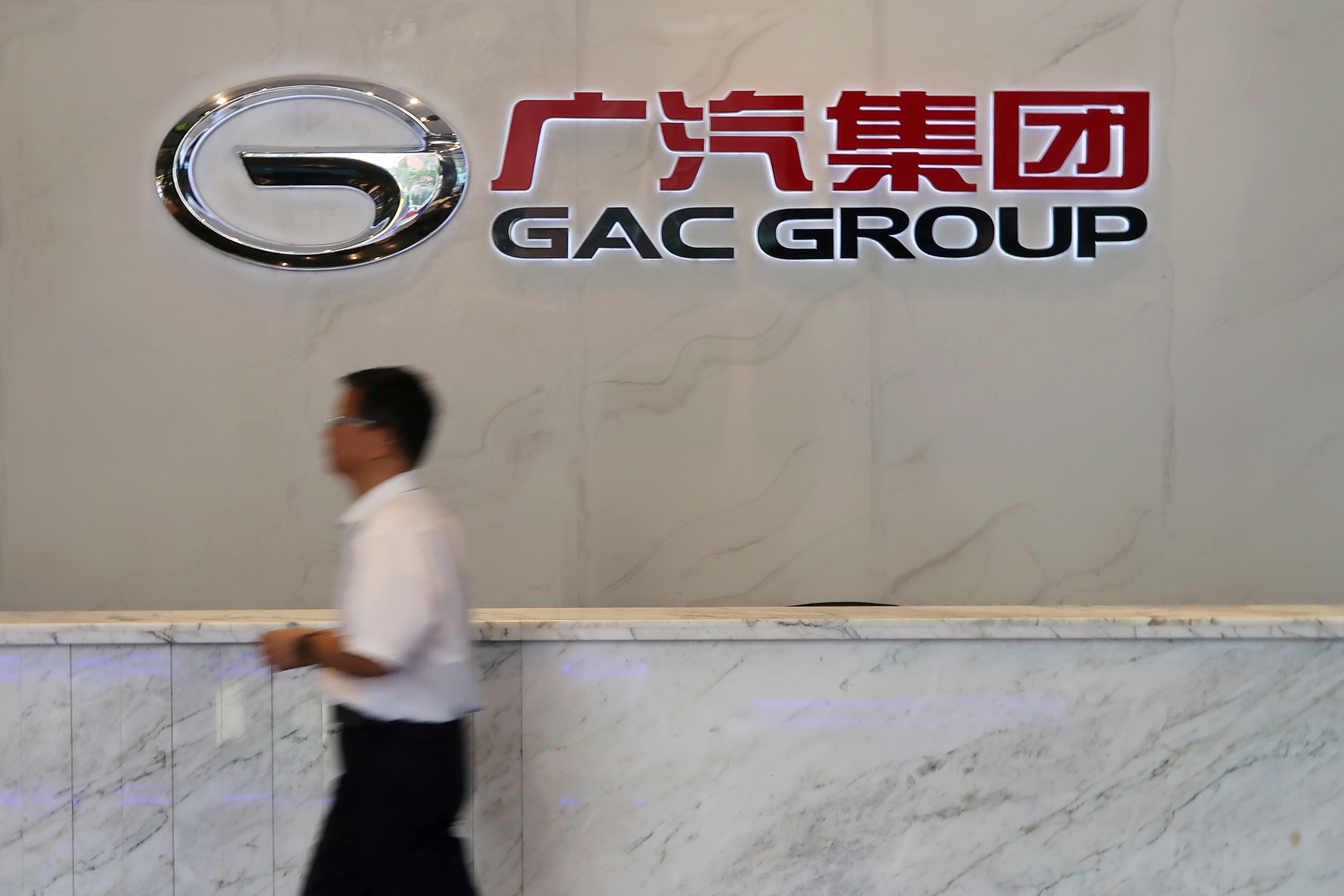 A man walks past the logo of Chinese automobile maker GAC Group at the company headquarters in Guangzhou, Guangdong province, China October 24, 2019. Picture taken October 24, 2019.  REUTERS/Yilei Sun