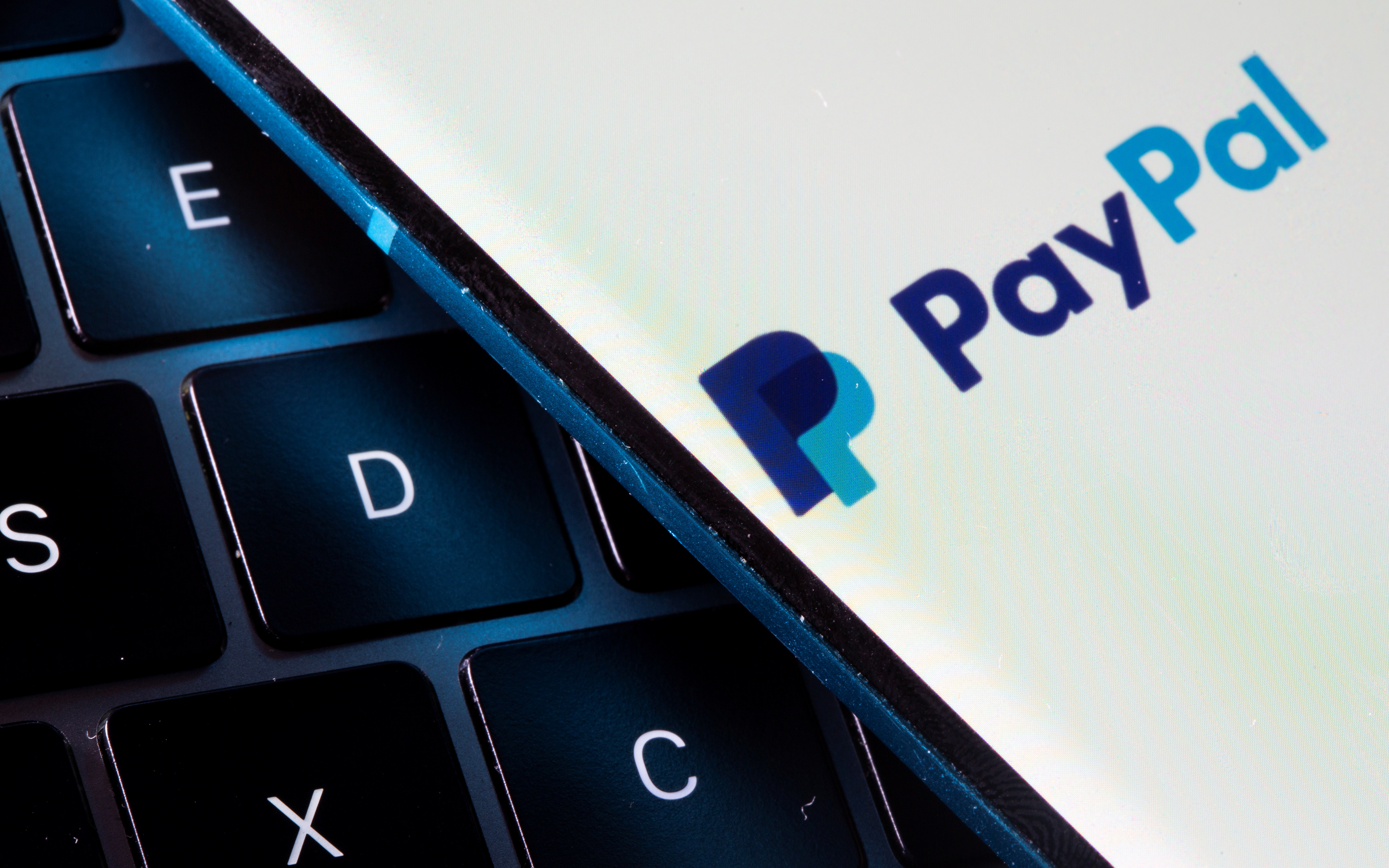 A smartphone with the PayPal logo is placed on a laptop in this illustration taken on July 14, 2021. REUTERS/Dado Ruvic/Illustration