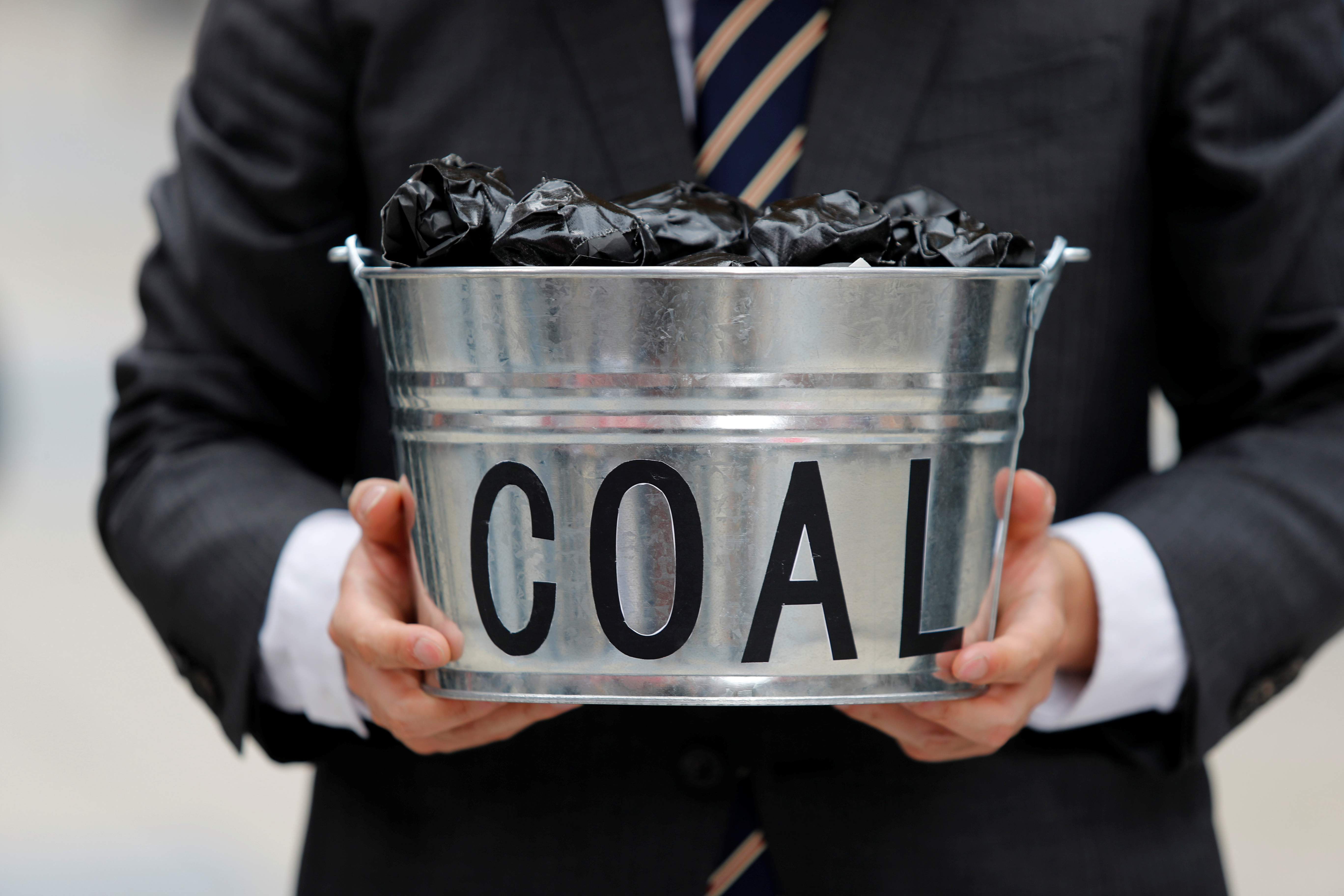A protester holds a bucket of coal during a demonstration demanding Japan to stop supporting coal at home and overseas, at the G20 Summit in Osaka, Japan, June 28, 2019. REUTERS/Jorge Silva