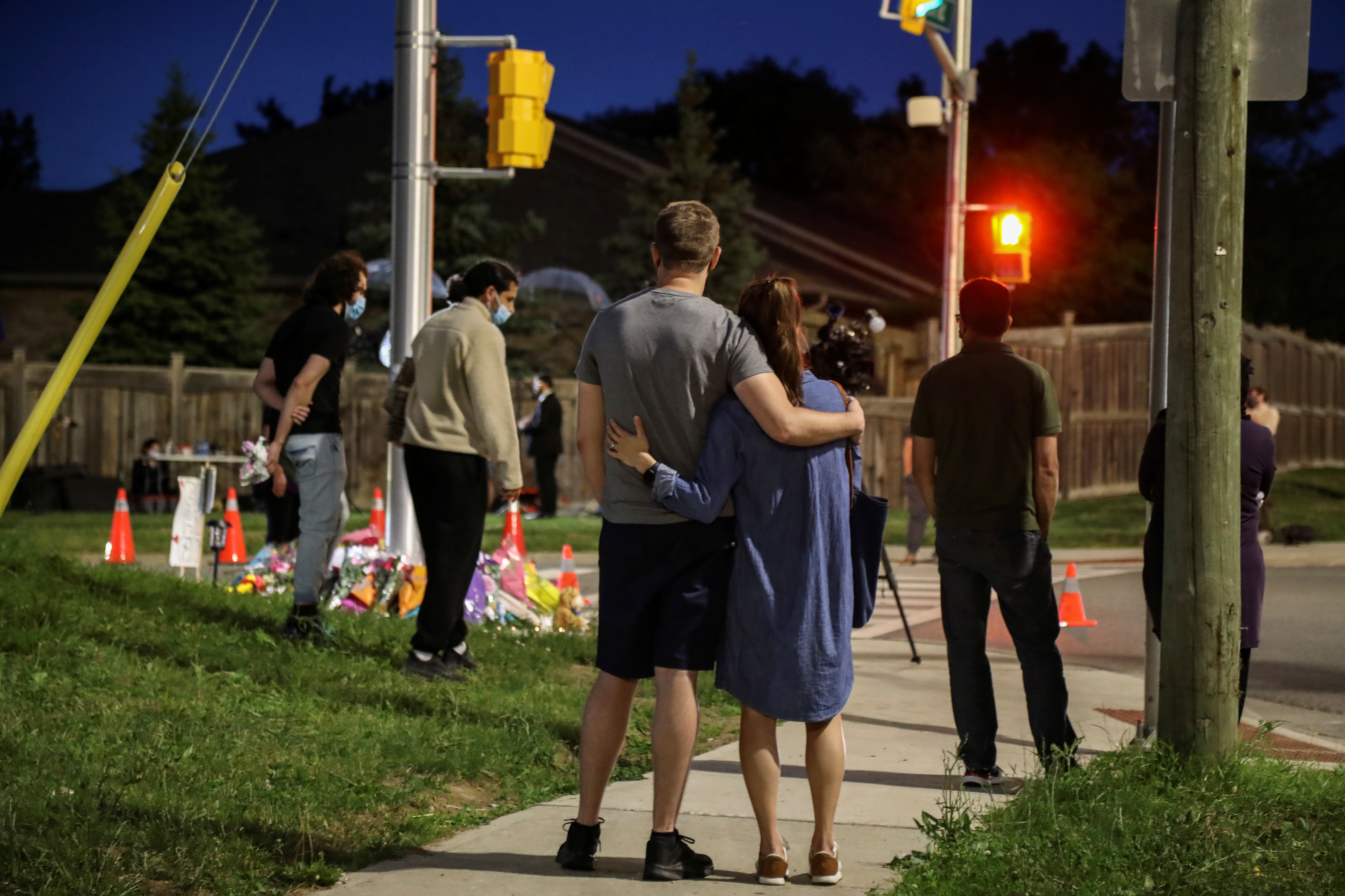 People and members of the media are seen at a makeshift memorial at the fatal crime scene where a man driving a pickup truck jumped the curb and ran over a Muslim family in what police say was a deliberately targeted anti-Islamic hate crime, in London, Ontario, Canada June 7, 2021. REUTERS/Carlos Osorio