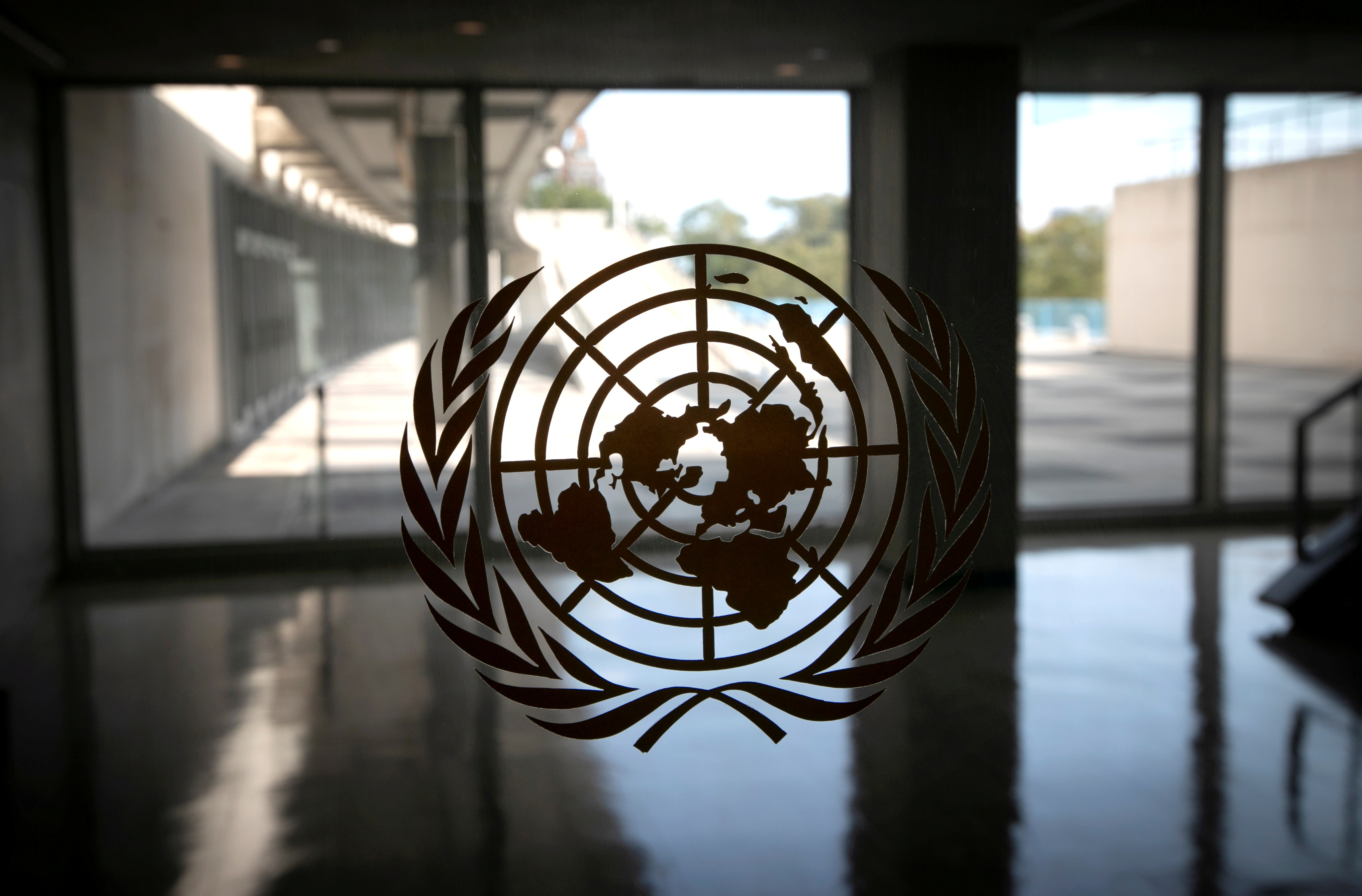 The United Nations logo is seen on a window in an empty hallway at United Nations headquarters during the 75th annual U.N. General Assembly high-level debate in New York, U.S., September 21, 2020. REUTERS/Mike Segar/File Photo