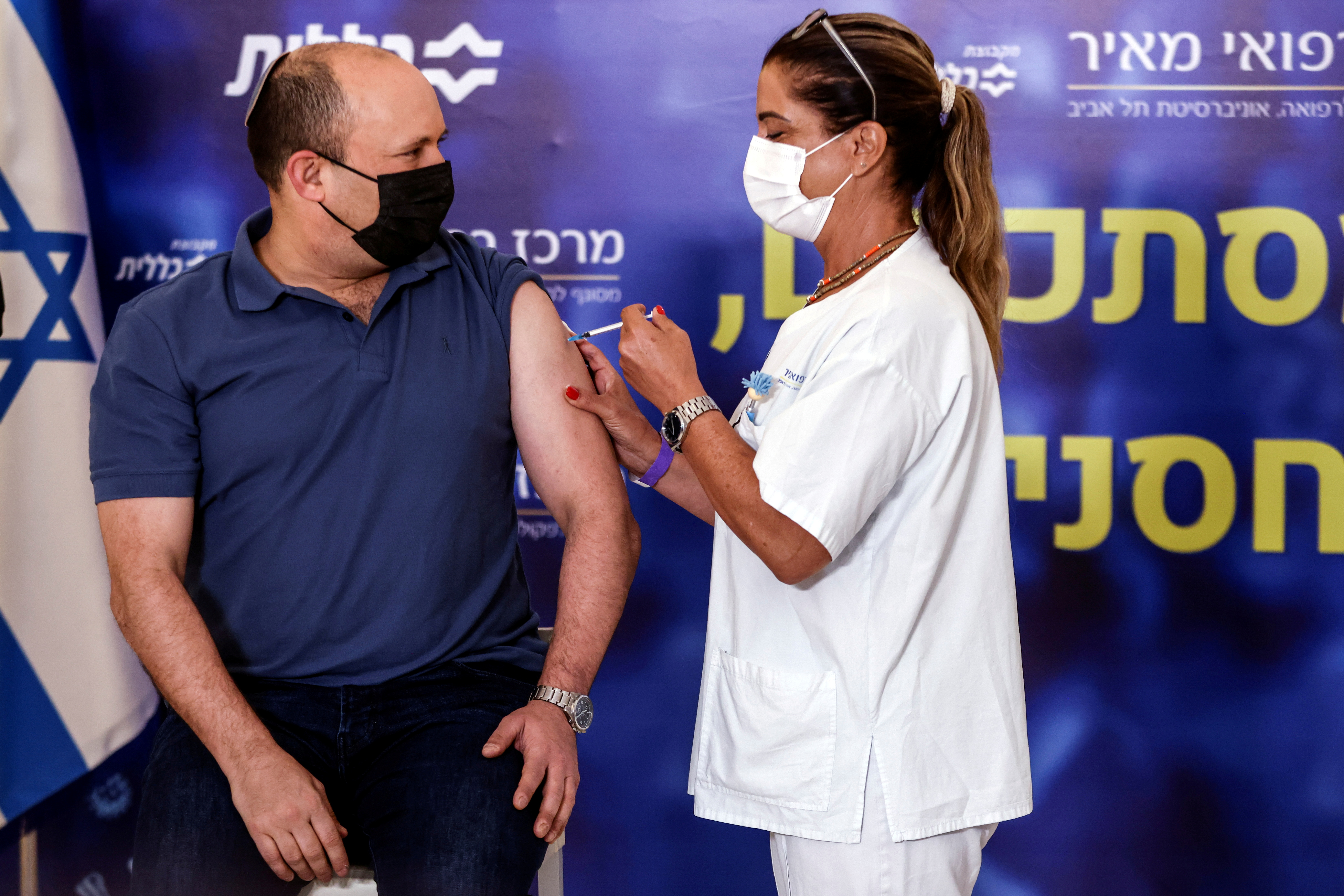 Israeli Prime Minister Naftali Bennett receives a third shot of the coronavirus disease (COVID-19) vaccine as the country launches booster shots for over 40 year-olds, in Kfar Saba, Israel August 20, 2021. REUTERS/Ronen Zvulun/File Photo
