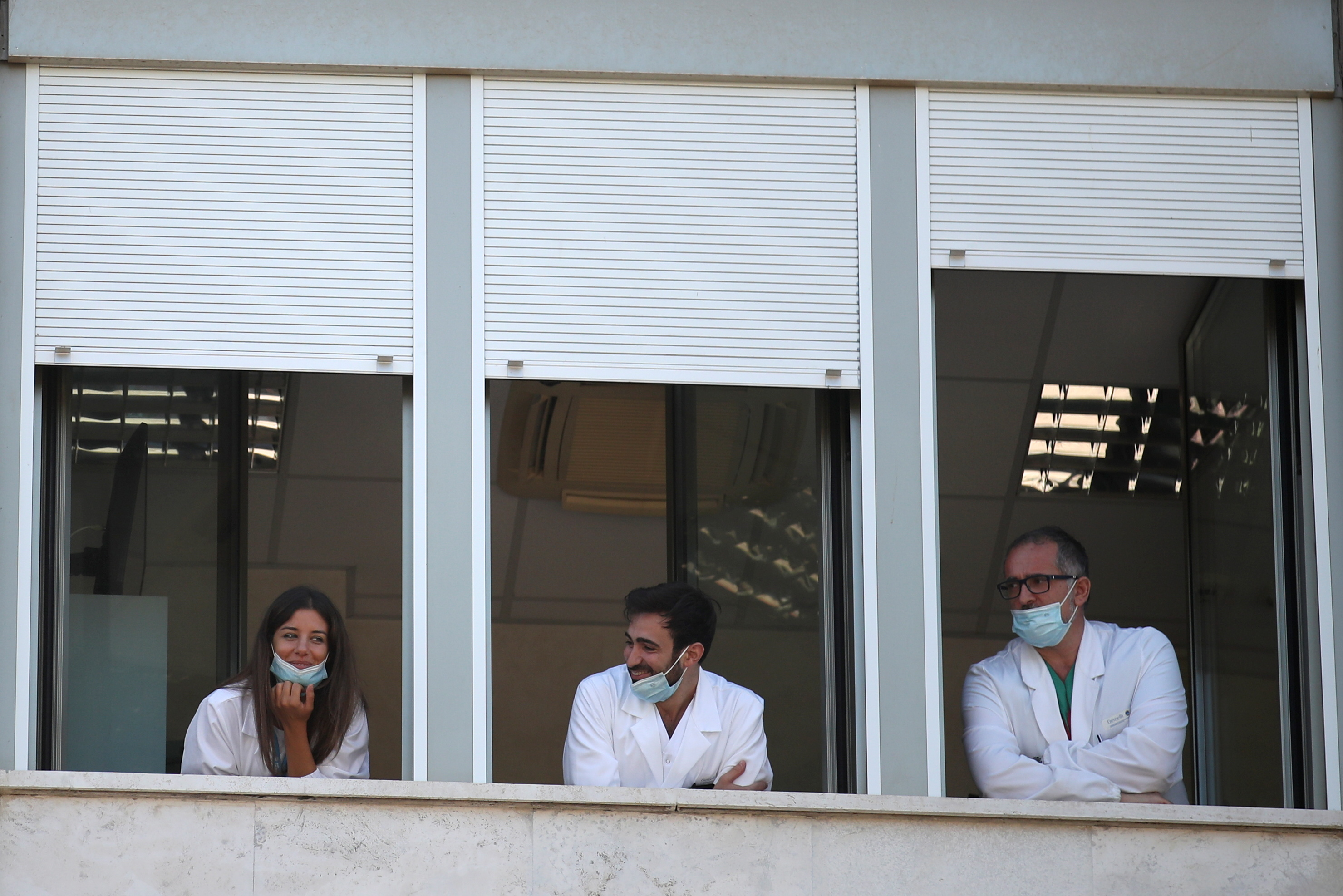 Healthcare workers look out the windows of the Gemelli hospital, from where Pope Francis is expected to lead the Angelus prayer, as he recovers following scheduled surgery on his colon, in Rome, Italy, July 11, 2021. REUTERS/Yara Nardi