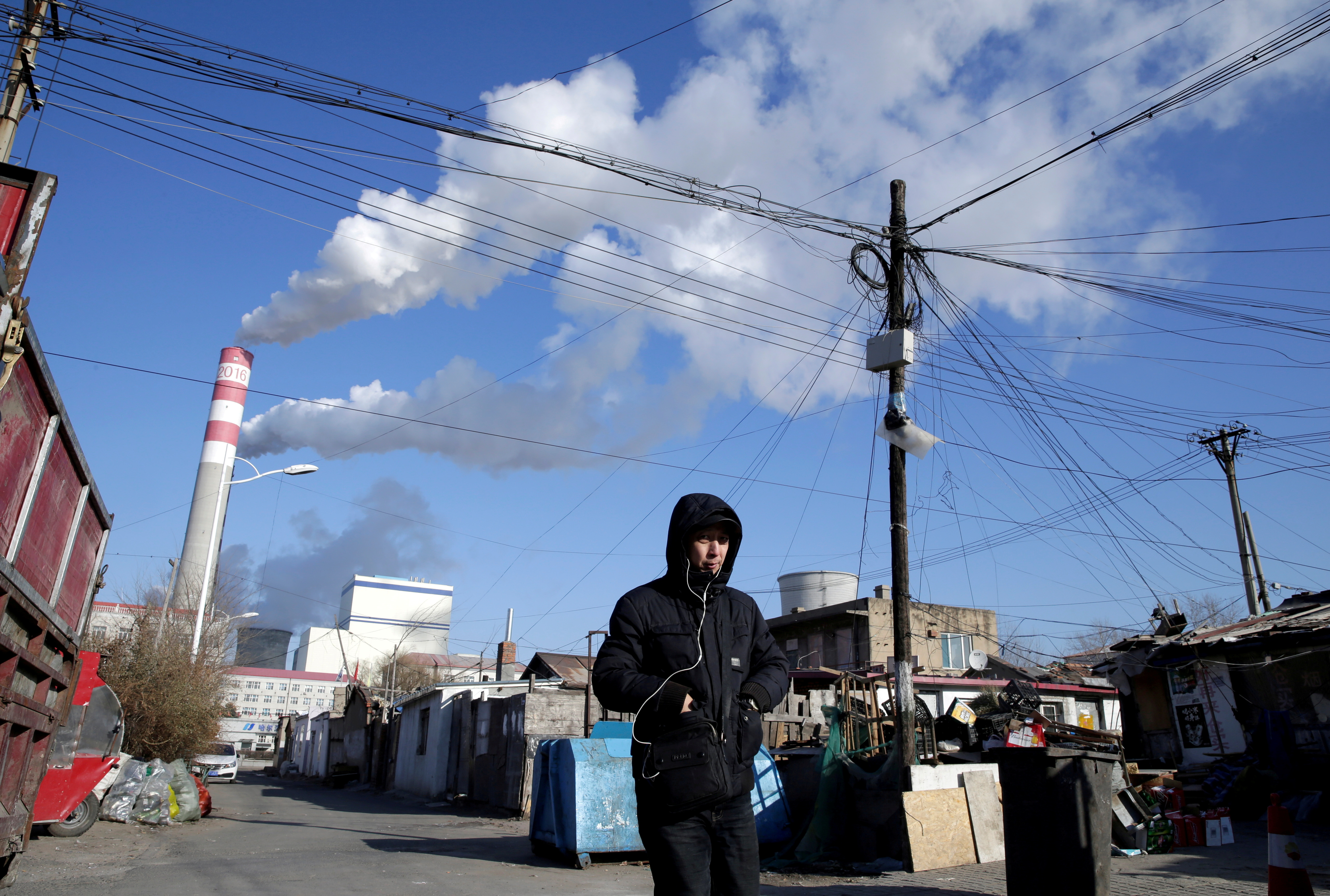 A man walks near a coal-fired power plant in Harbin, Heilongjiang province, China, November 27, 2019. REUTERS/Jason Lee/File Photo