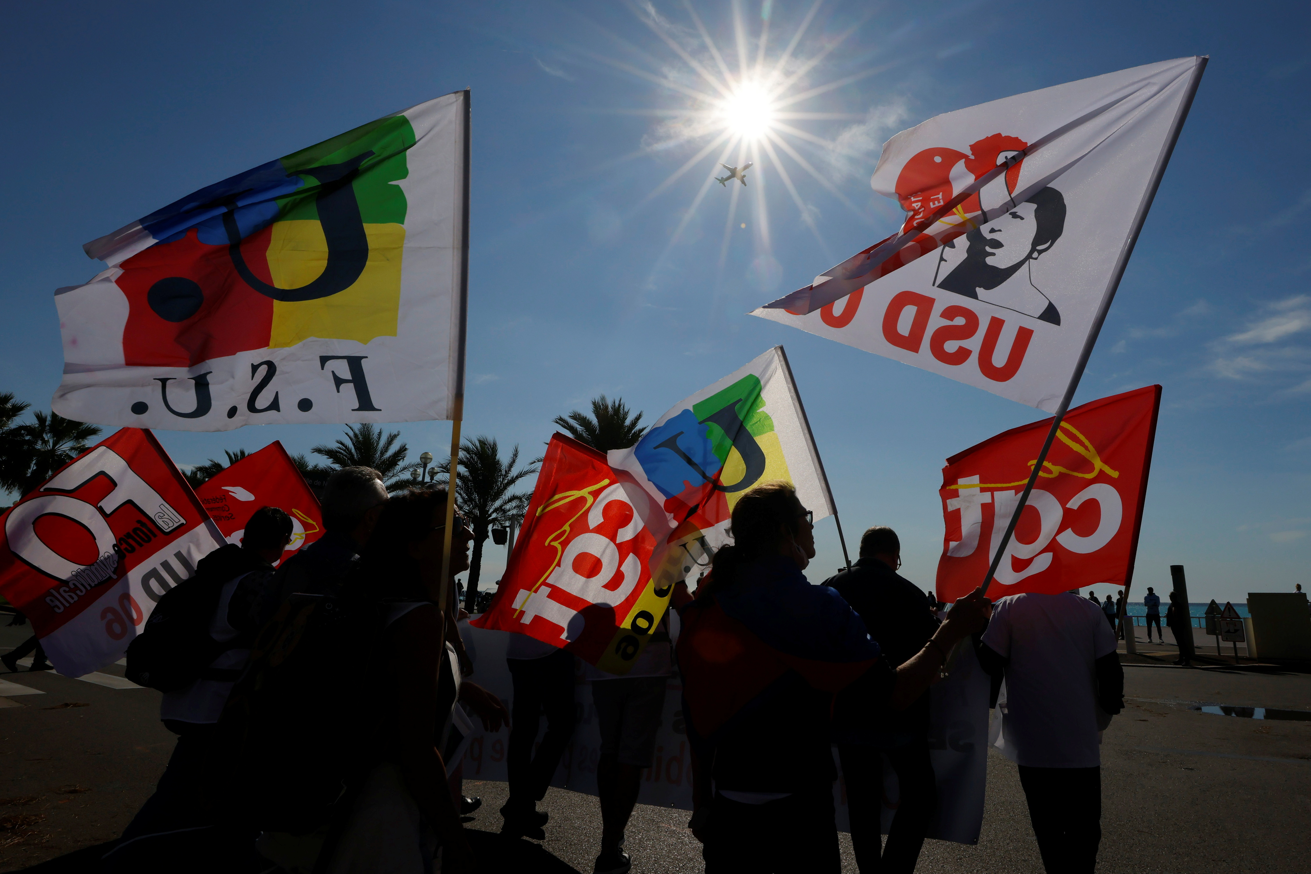 Protestors hold CGT labour union, Force Ouvriere (FO) labour union and  Federation Syndicale Unitaire (FSU) union flags during a demonstration in Nice as part of a day of strikes and protests against French government's economic and social policies, France, October 5, 2021.   REUTERS/Eric Gaillard