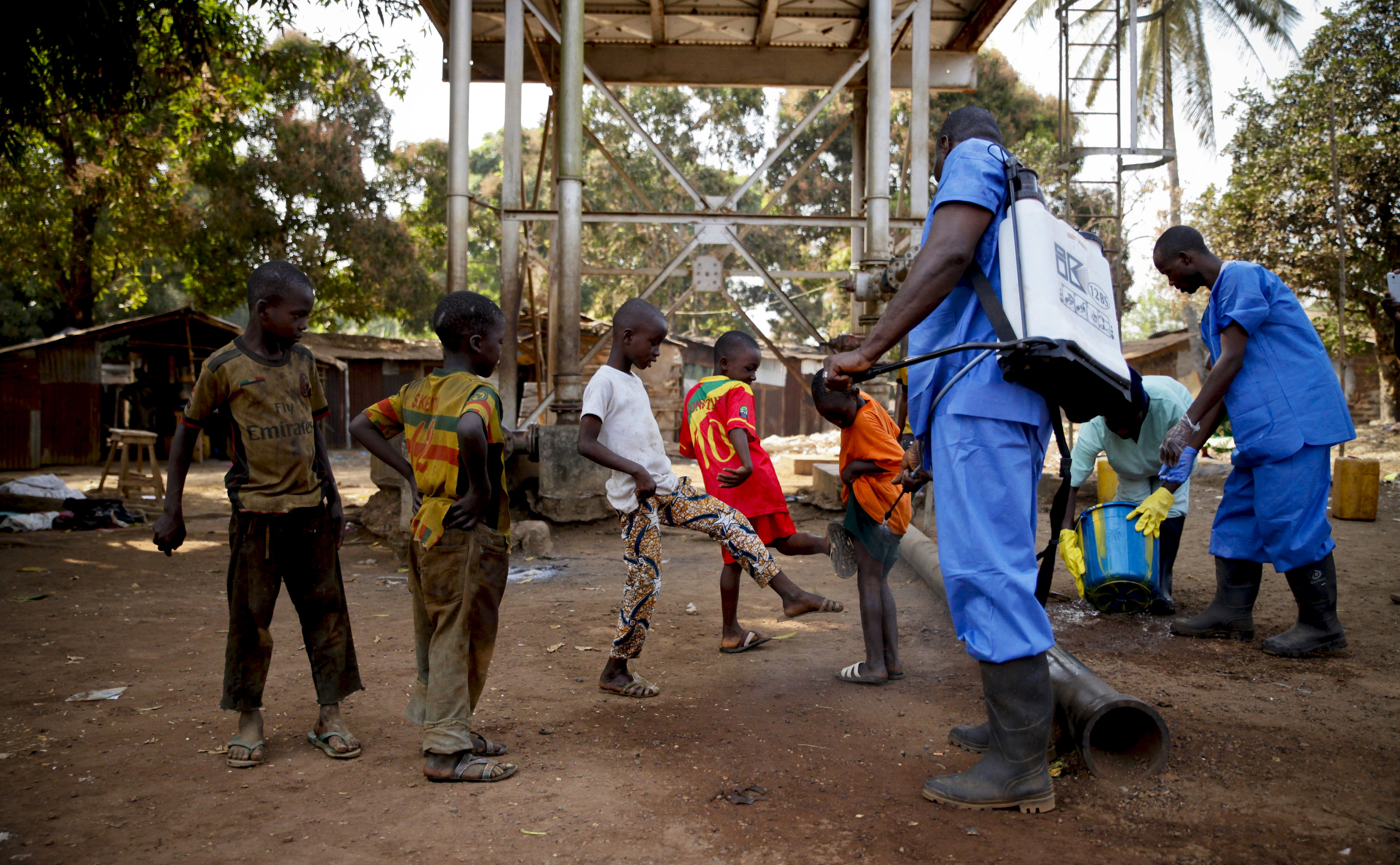Children come forward to get their feet disinfected after a Red Cross worker explained that they are spraying bleach, and not spraying the village with the Ebola virus, in Forecariah, on January 30, 2015. REUTERS/Misha Hussain