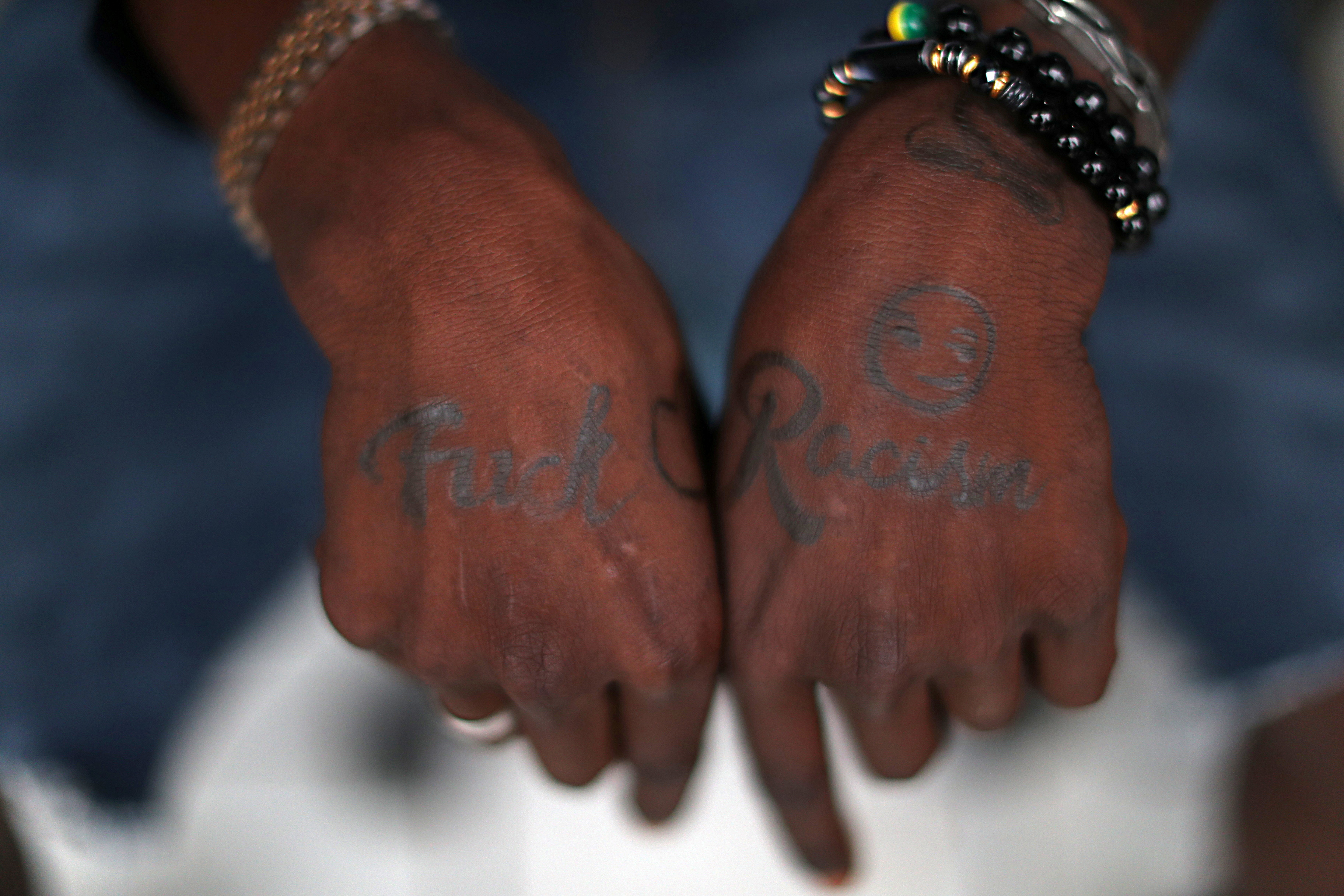 SENSITIVE MATERIAL. THIS IMAGE MAY OFFEND OR DISTURB  A migrant from Haiti shows the tattoos on his hands, as thousands of Haitians were detained, deported or expelled from a camp on Mexico's frontier with Texas last week and others traveled west to the border city of Tijuana while aiming to avoid a crackdown on a recent spike in migrant traffic, in Tijuana, Mexico September 27, 2021. REUTERS/Edgard Garrido