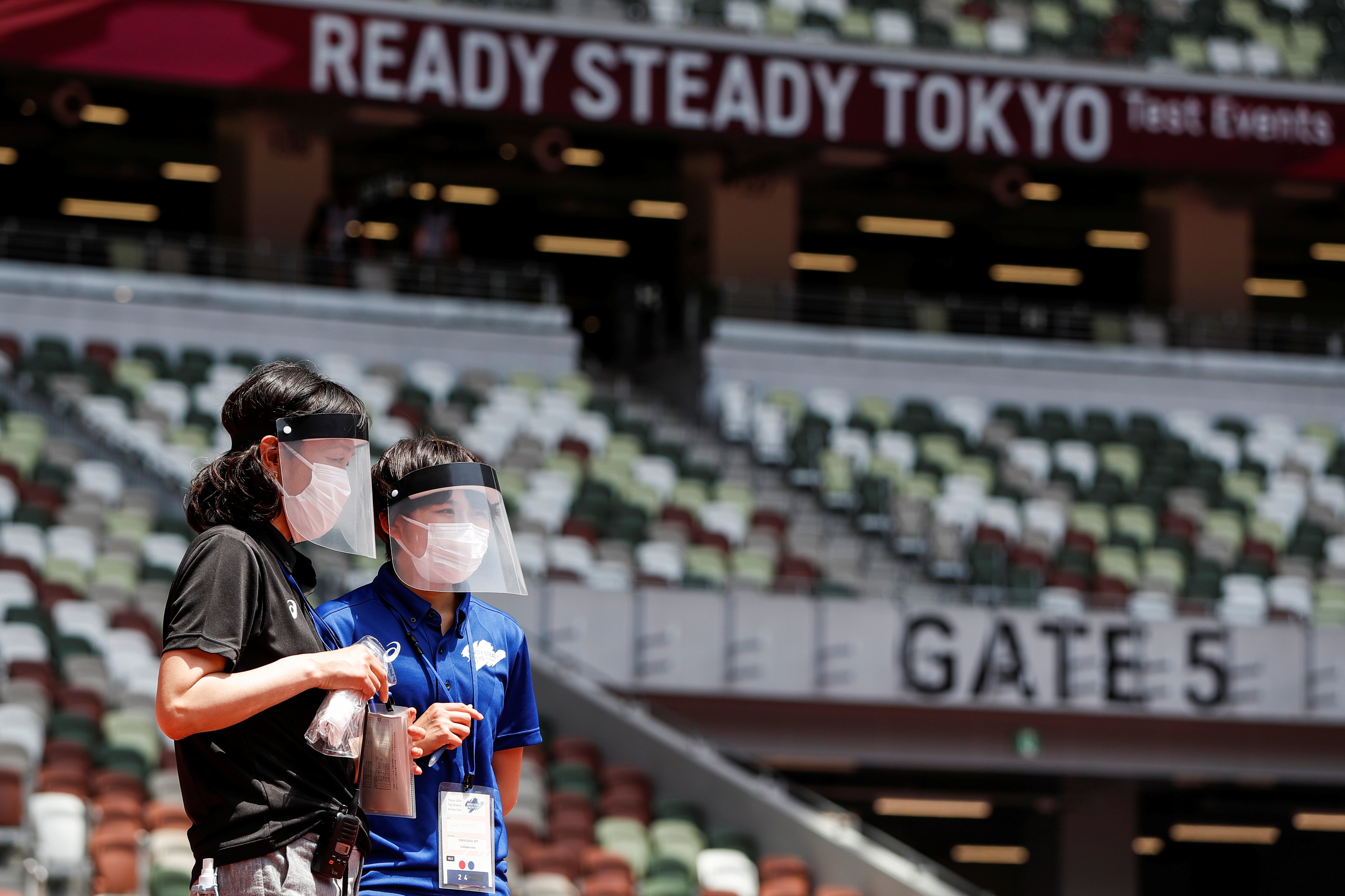 Olympics - Tokyo 2020 Olympic Games Test Event - Athletics - Olympic Stadium, Tokyo, Japan - May 9, 2021.     Officials wear face masks and shields as a preventive measure against the coronavirus disease (COVID-19) during the morning session of the Athletics test event. REUTERS/Issei Kato