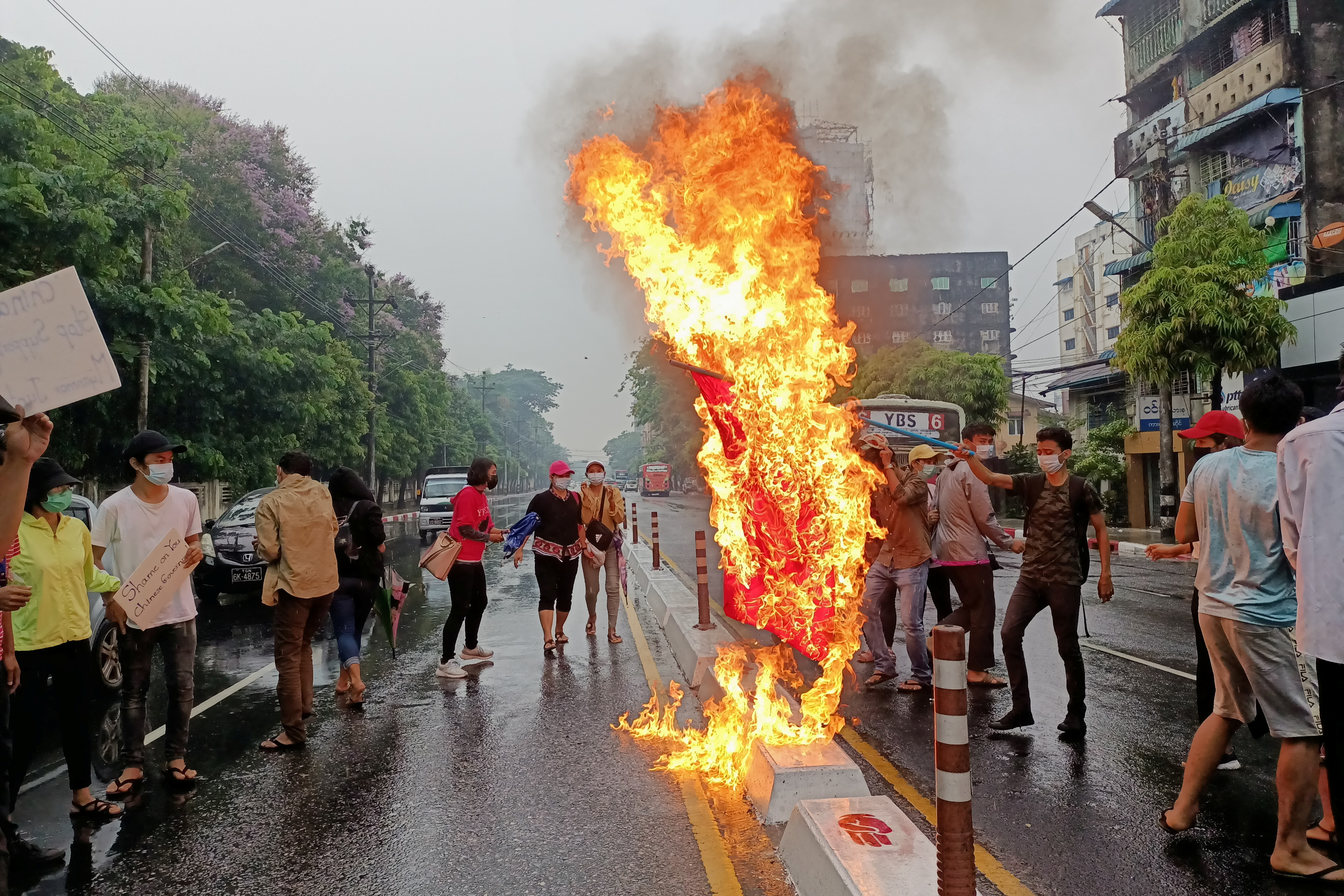 Anti-coup protesters burn a Chinese flag in Yangon, Myanmar  April 5, 2021. REUTERS/Stringer