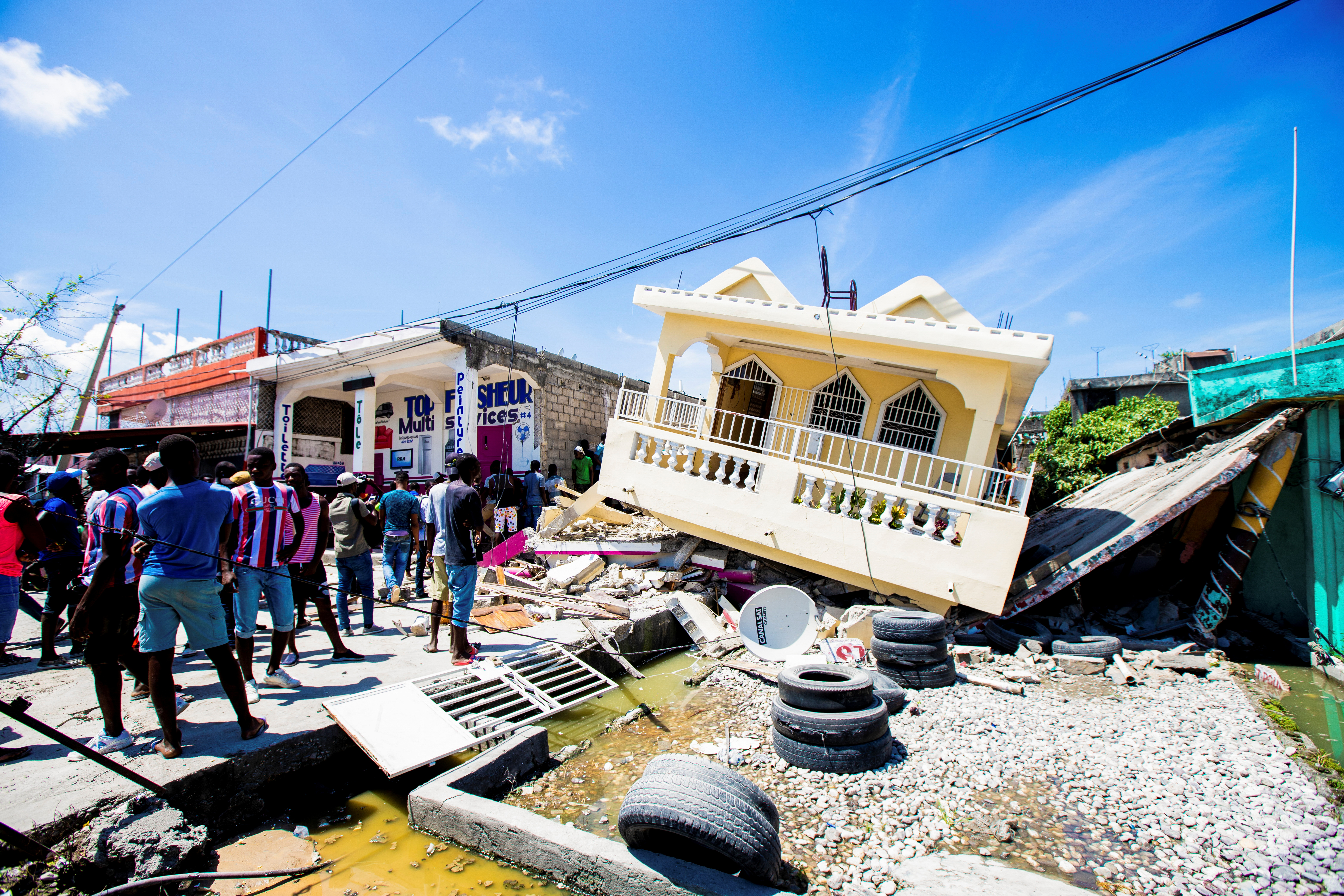 People stand next to a house destroyed following a 7.2 magnitude earthquake in Les Cayes, Haiti August 14, 2021. REUTERS/Ralph Tedy Erol NO RESALES. NO ARCHIVES