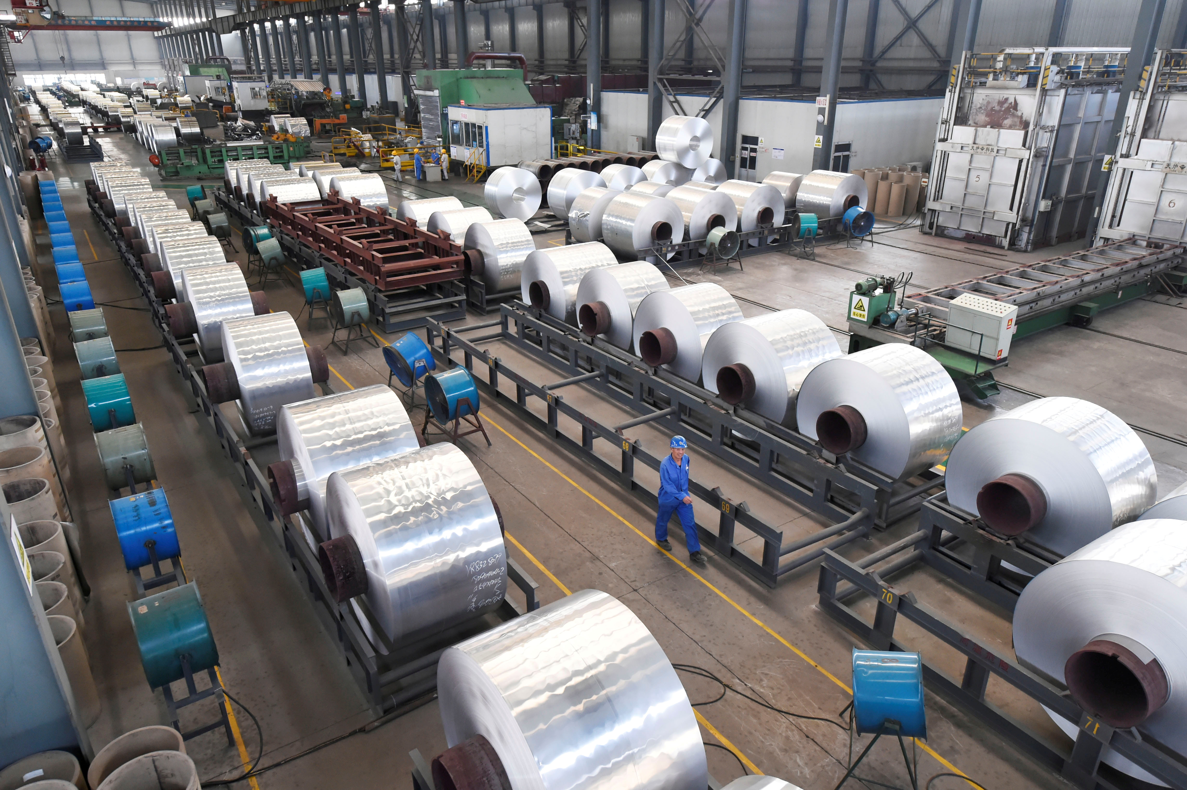 Workers are seen next to aluminium rolls at a plant in Binzhou, Shandong province, China September 13, 2018. Picture taken September 13, 2018. REUTERS/Stringer