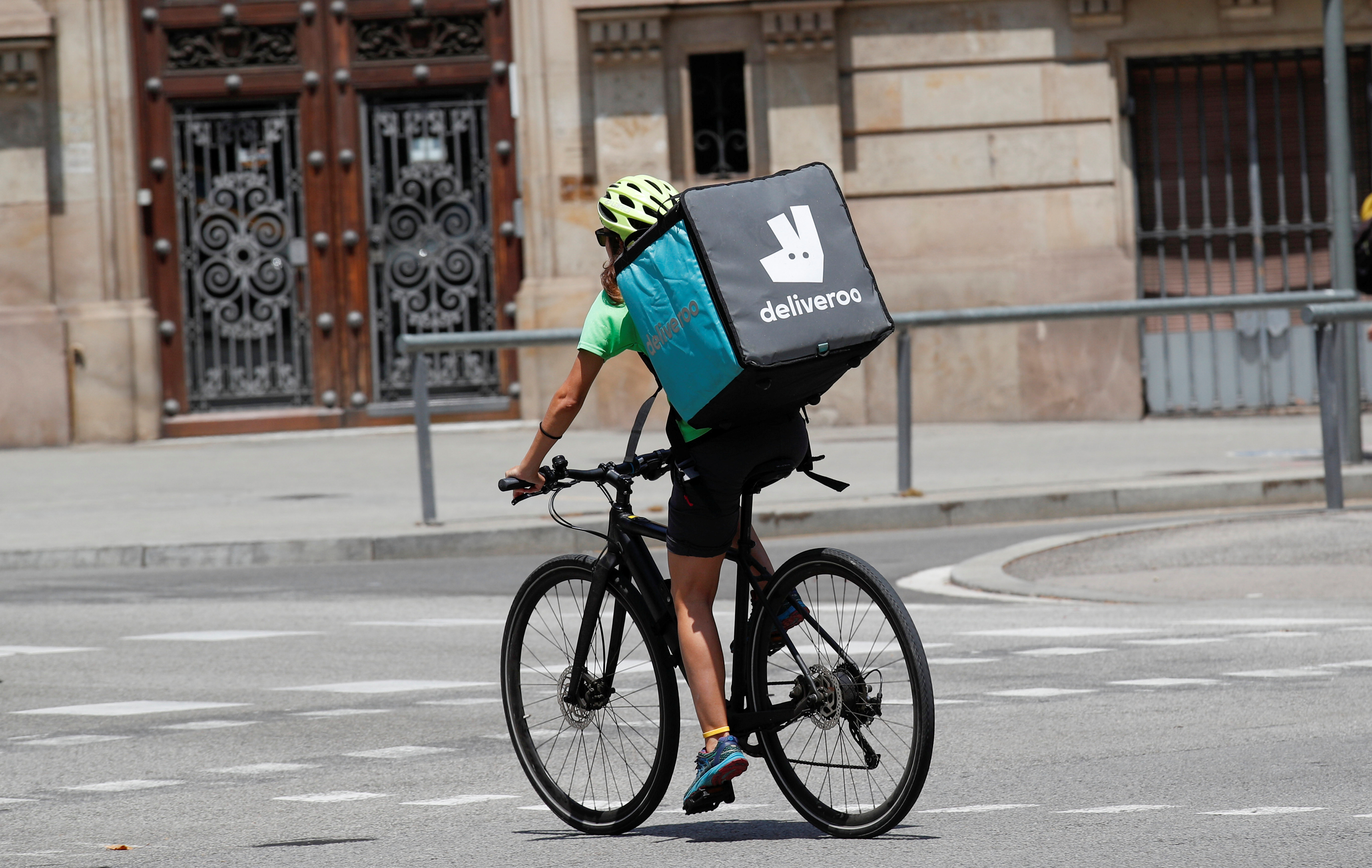 A biker wearing a Deliveroo backpack drives in the central Barcelona, Spain, July 23, 2019. REUTERS/Albert Gea/File photo