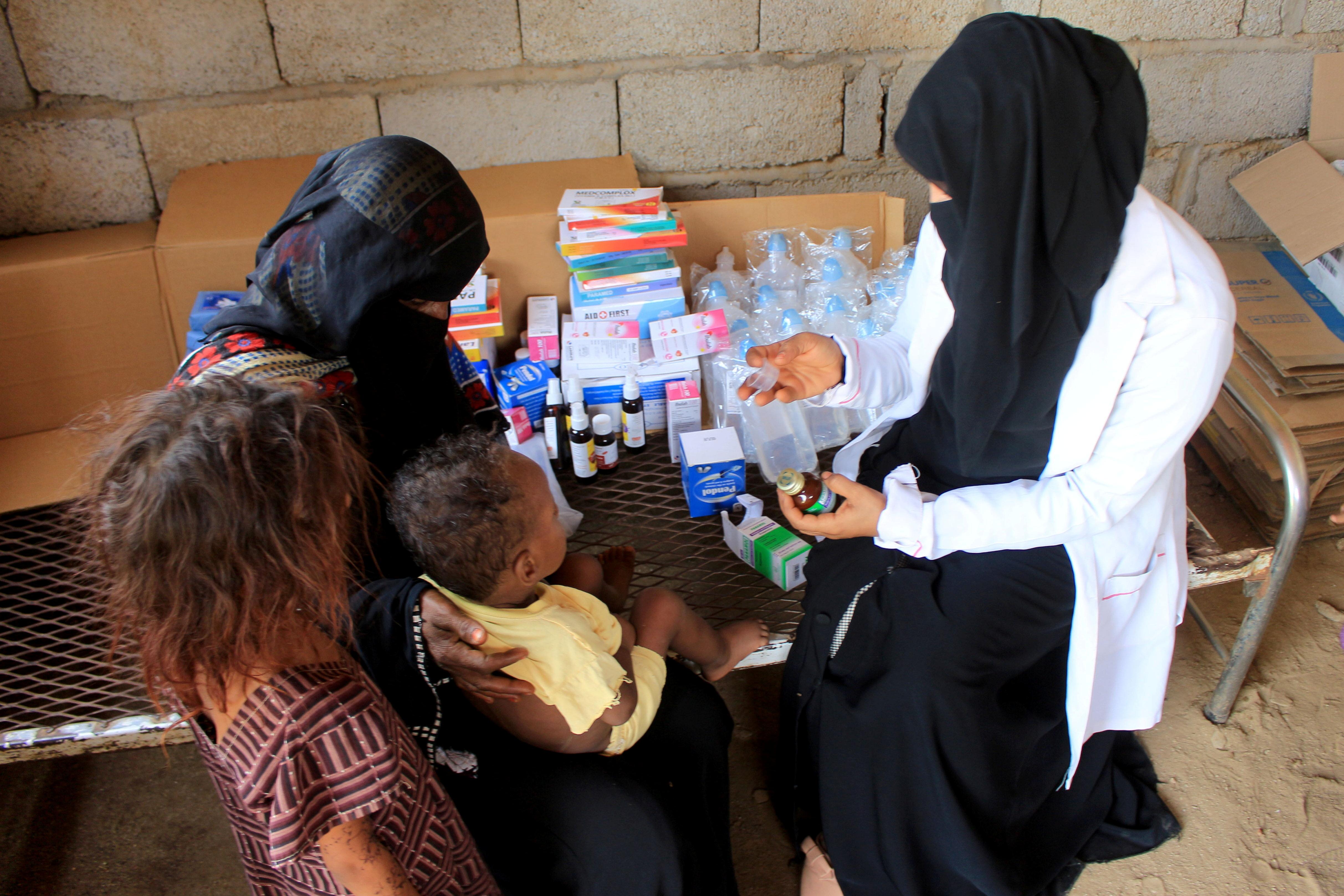 Volunteer health worker Ashwaq Mahmoud checks a medicine as she helps a child in Abs, Yemen September 13, 2021.   REUTERS/Eissa Alragehi
