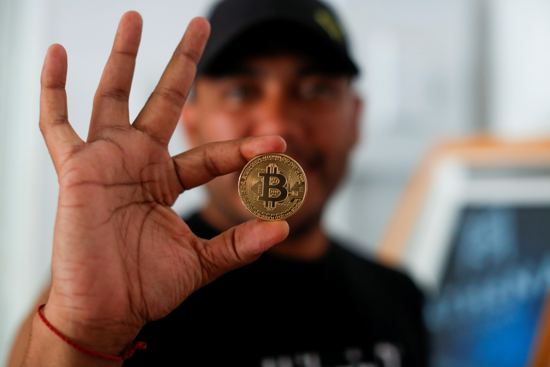 Bitcoin enthusiast Carlos Bonilla shows a physical representation of the cryptocurrency, at a Bitcoin Beach support office at El Zonte Beach in Chiltiupan, El Salvador June 10, 2021. REUTERS/Jose Cabezas