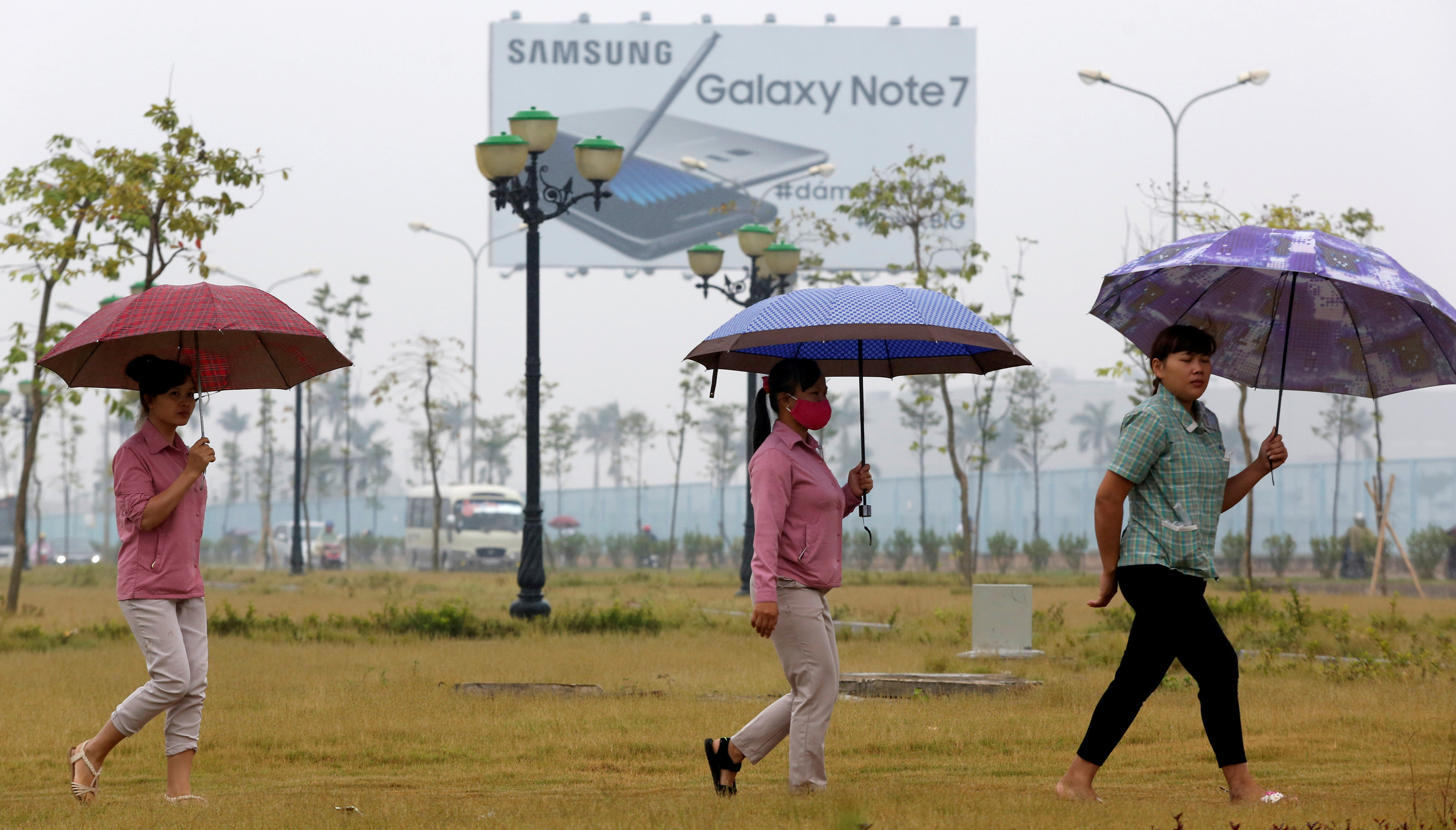 Employees pass a billboard advertisement for the Samsung Galaxy Note 7 on the way to work at the Samsung factory in Thai Nguyen province, north of Hanoi, Vietnam October 13, 2016. REUTERS/Kham