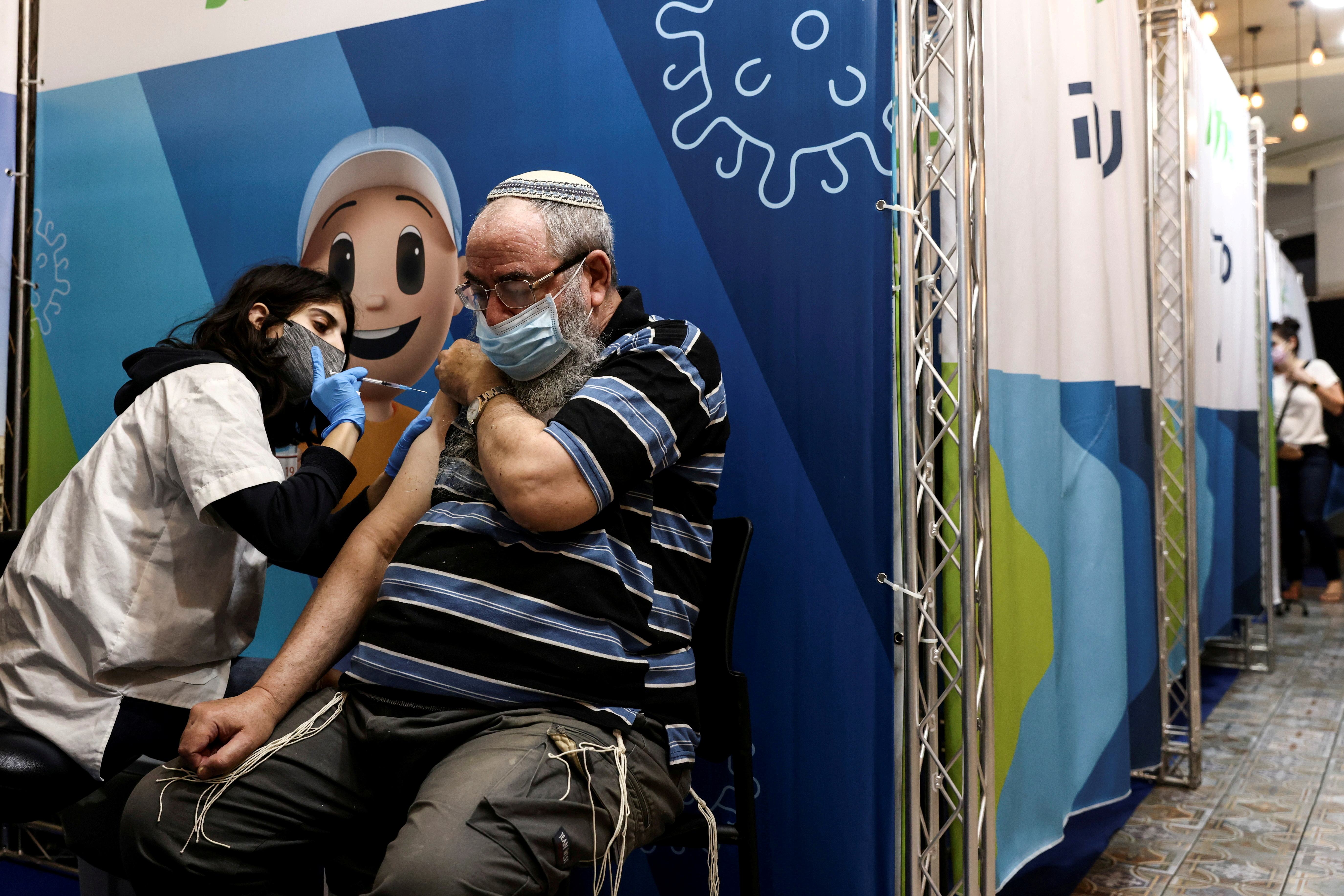 A man receives his third dose of the coronavirus disease (COVID-19) vaccine in Jerusalem, August 15, 2021. REUTERS/ Ronen Zvulun/File Photo