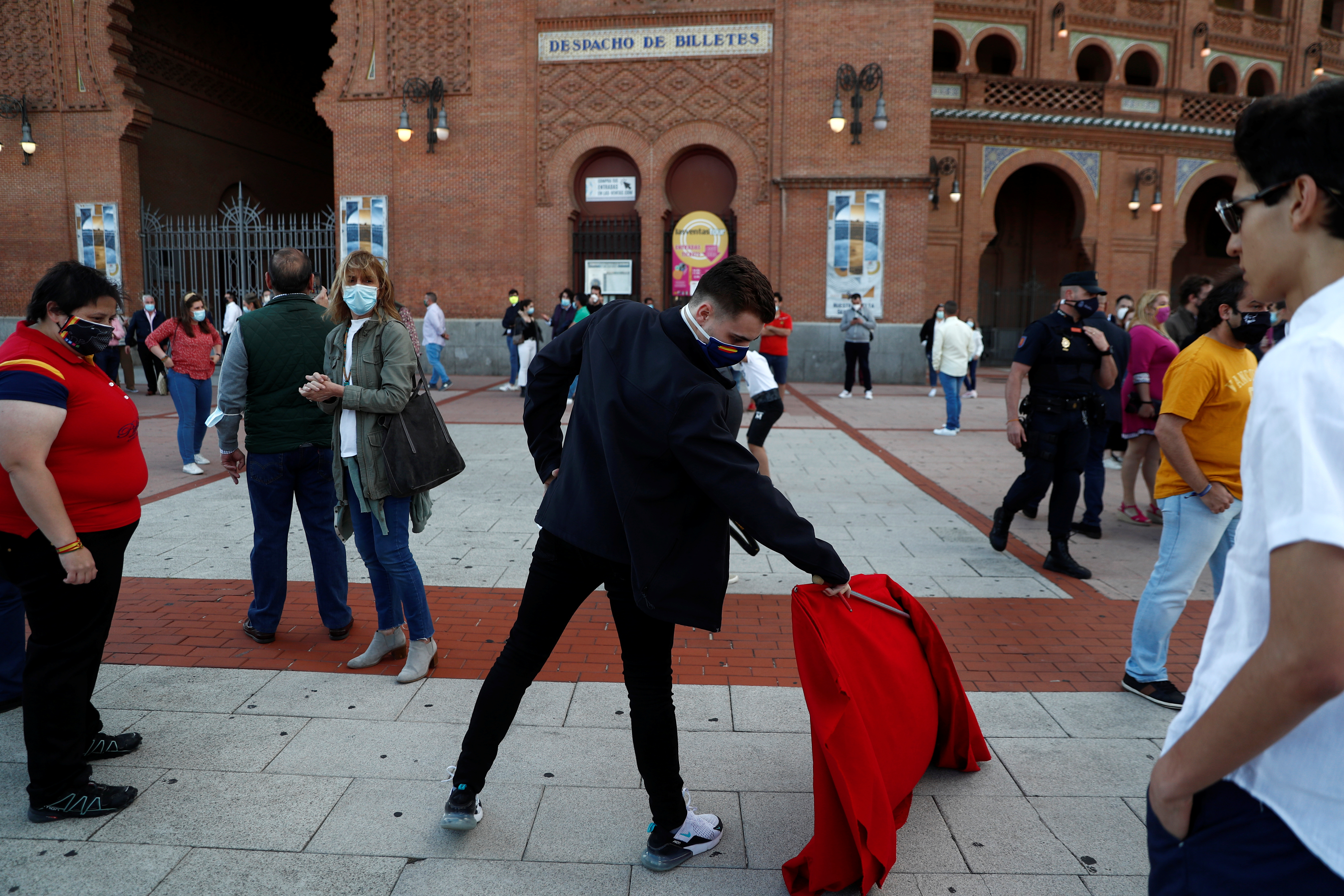 A man performs a pass with a cape as people stand outside Las Ventas bullring to show support for bullfighting, following the impact of the coronavirus disease (COVID-19) outbreak which led to the cancellation of bullfights, in Madrid, Spain, June 13, 2020. REUTERS/Susana Vera