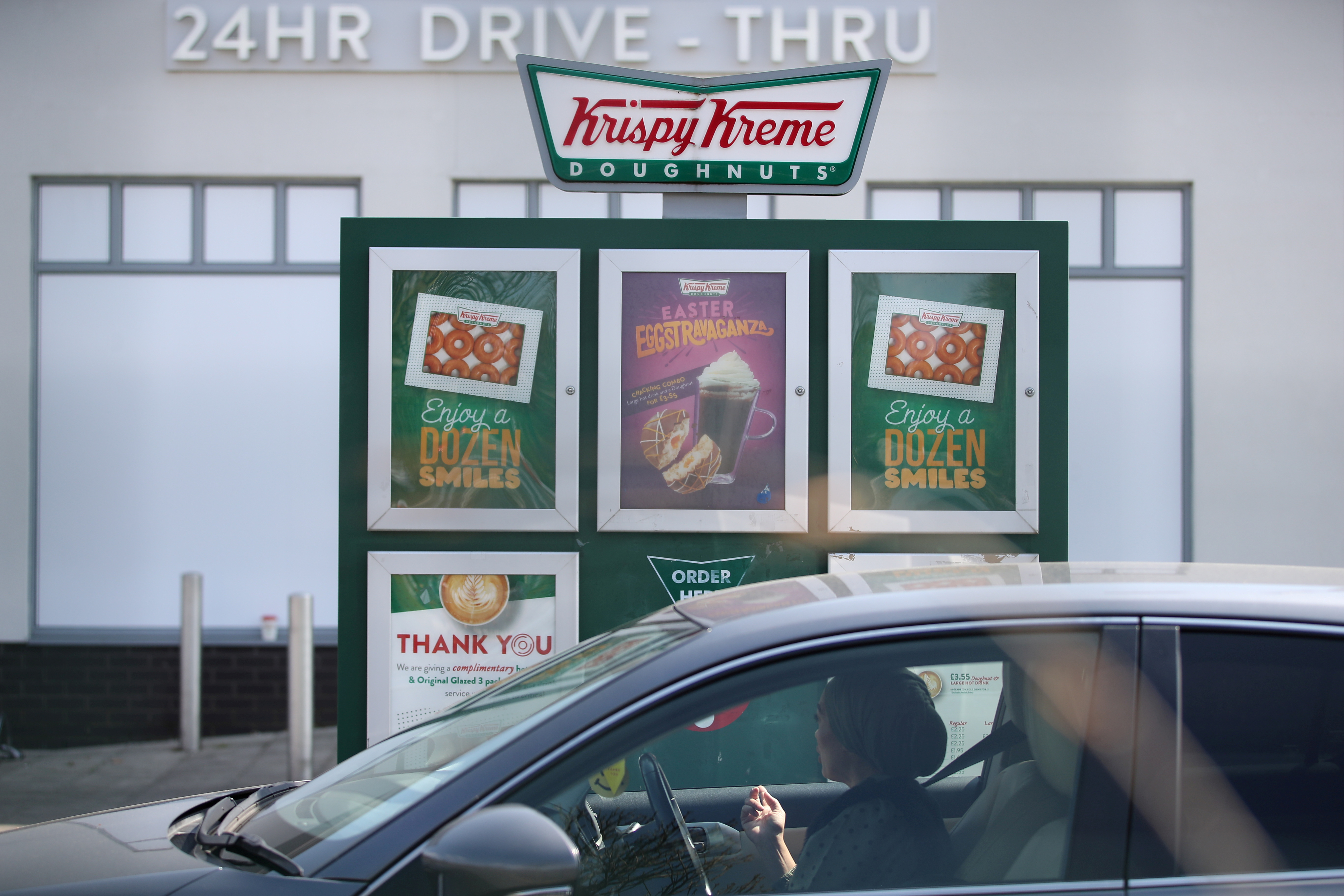 A woman in a car looks at a menu at a drive-thru Krispy Kreme at Trafford Park after opening their store to serve NHS staff and essential workers free doughnuts as the spread of the coronavirus disease (COVID-19) continues, Manchester, Britain, April 17, 2020. REUTERS/Molly Darlington/File Photo