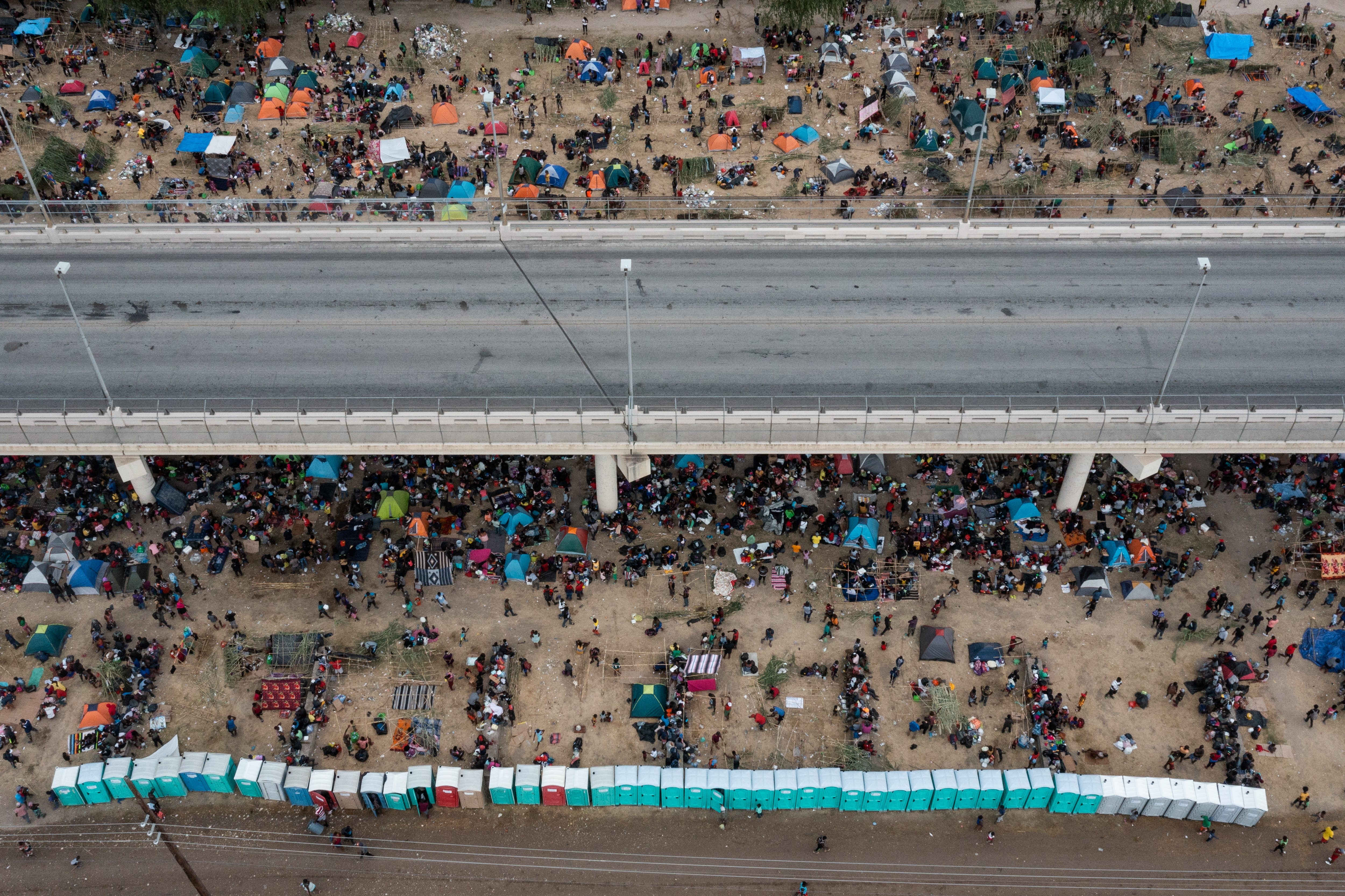 Some thousands of migrants take shelter as they await to be processed near the Del Rio International Bridge after crossing the Rio Grande river into the U.S. from Ciudad Acuna in Del Rio, Texas, U.S. September 18, 2021. Picture taken with a drone. REUTERS/Adrees Latif