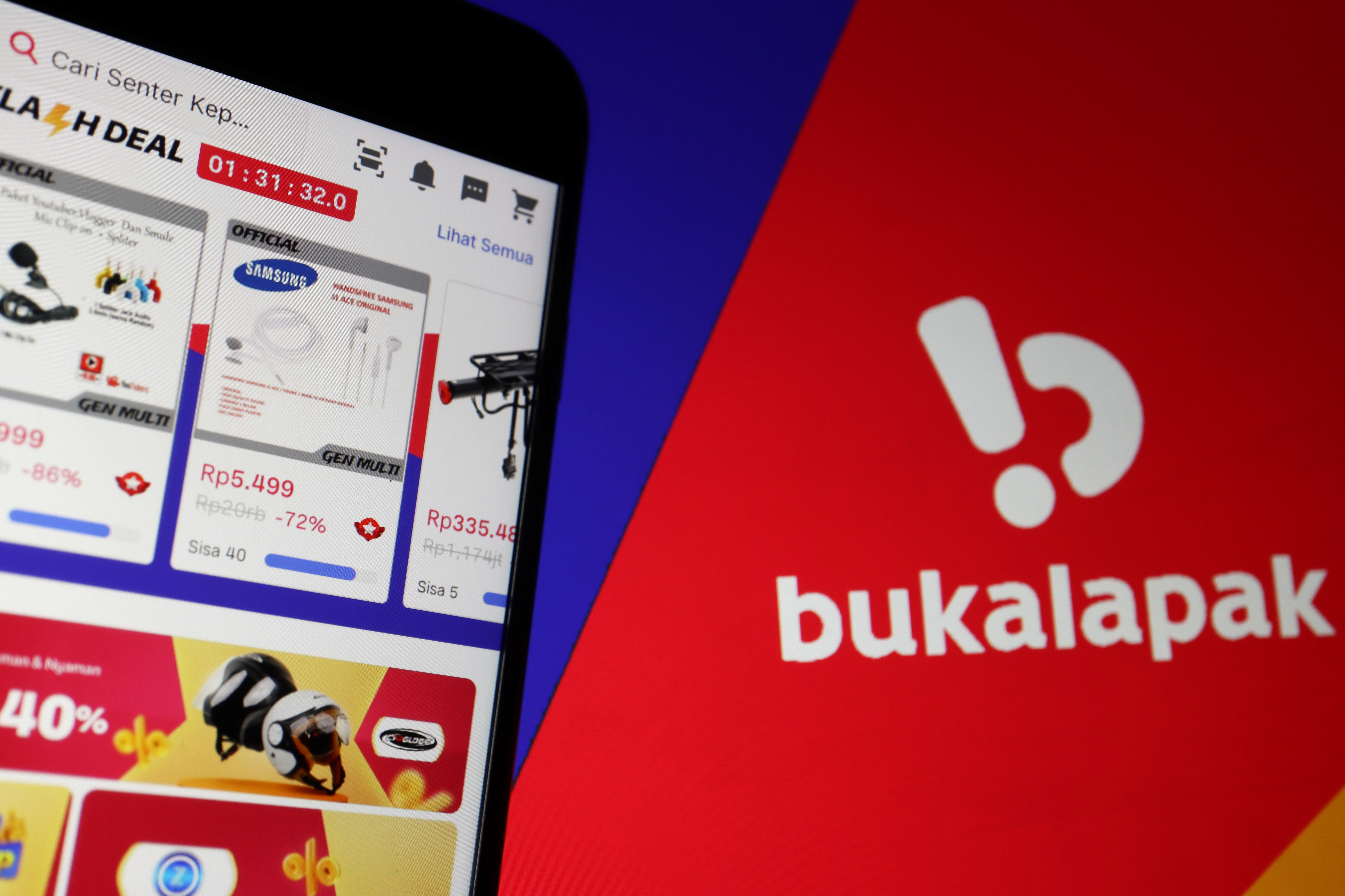 The app of Indonesian e-commerce company Bukalapak is seen on a mobile phone next to its logo displayed in this illustration picture taken July 14, 2021. REUTERS/Florence Lo/Illustration
