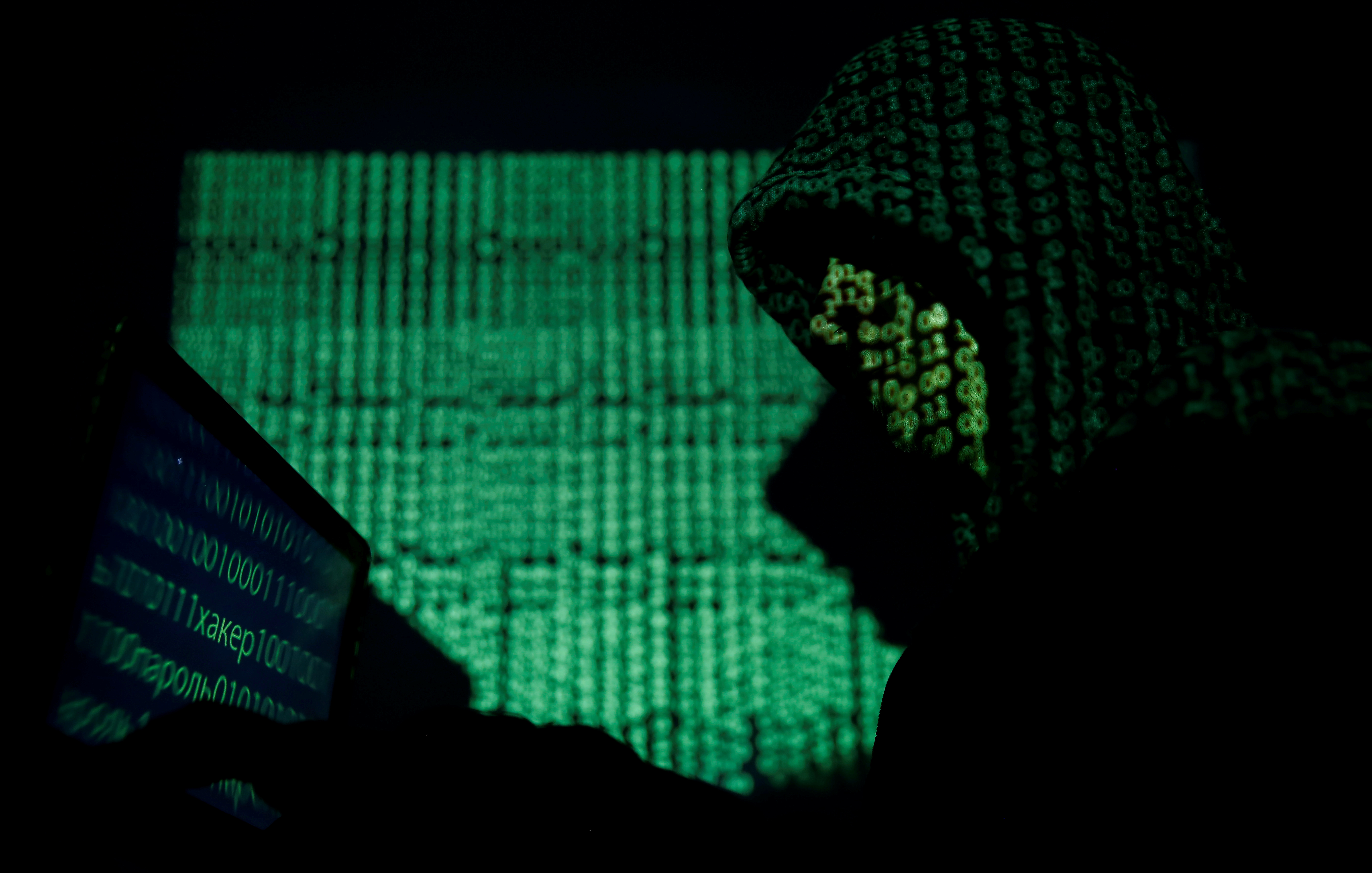 A hooded man holds a laptop computer as cyber code is projected on him in this illustration picture taken on May 13, 2017. REUTERS/Kacper Pempel