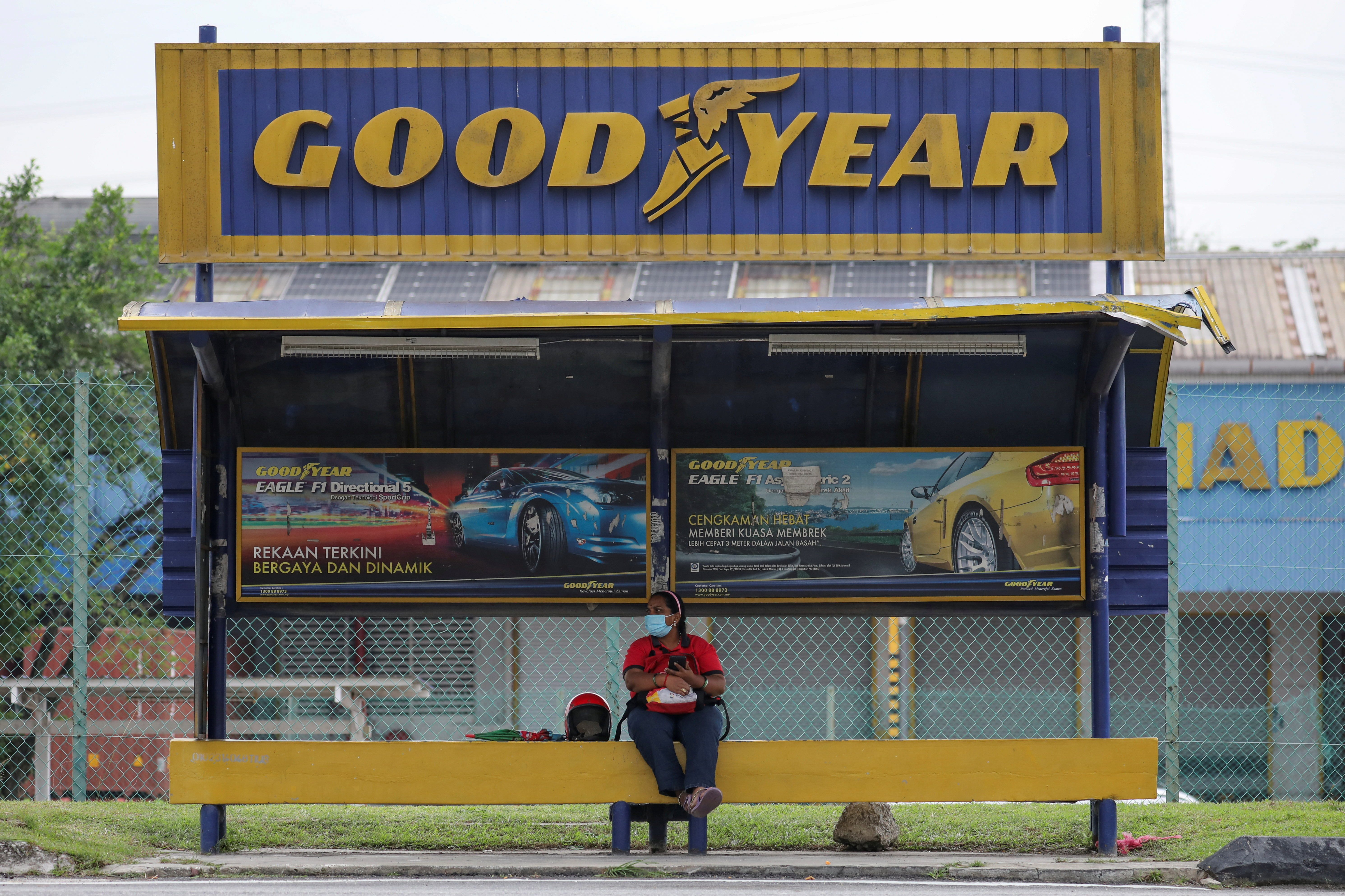 A woman sits at a bus stop outside Goodyear factory in Shah Alam, Malaysia May 6, 2021. REUTERS/Lim Huey Teng