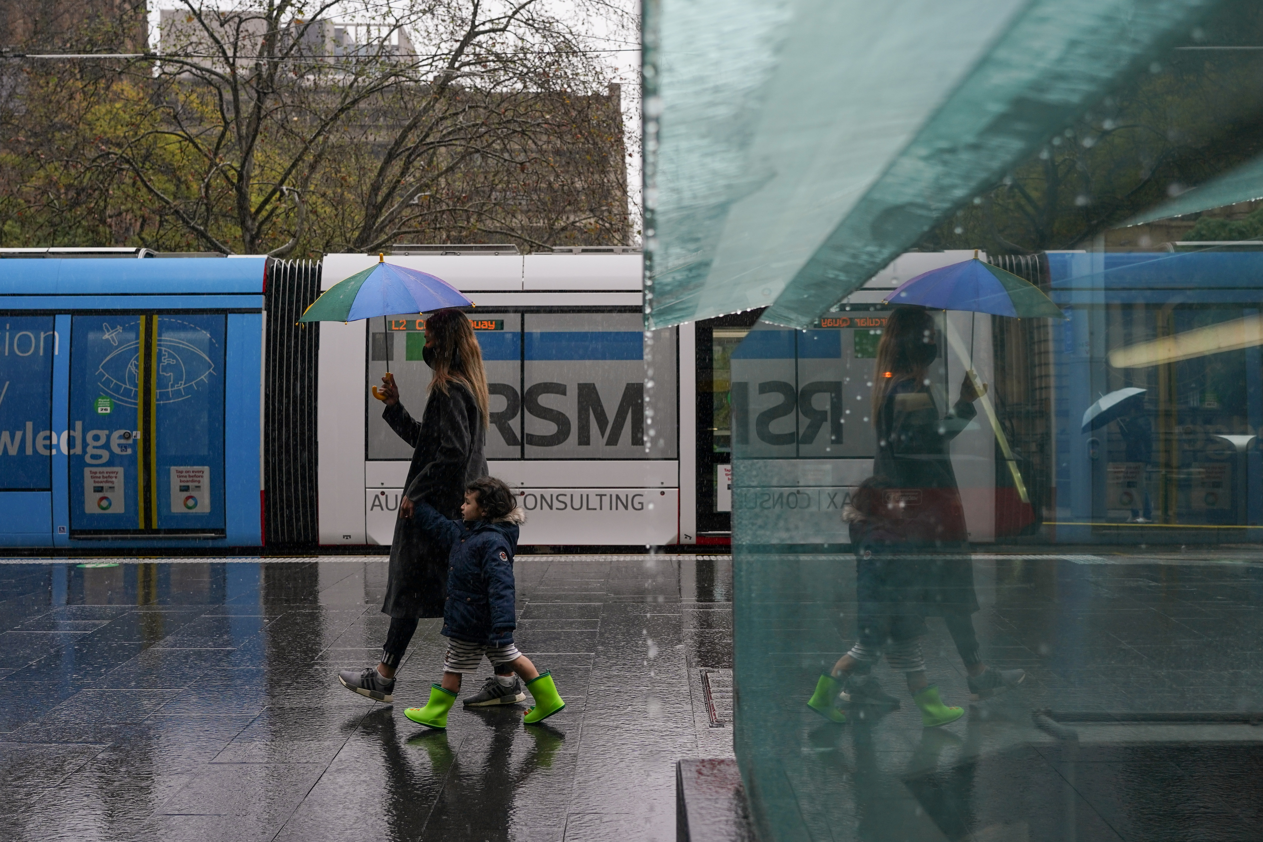 A masked woman with an umbrella walks with a child through the quiet city centre during a lockdown to curb the spread of a coronavirus disease (COVID-19) outbreak in Sydney, Australia, August 24, 2021.  REUTERS/Loren Elliott