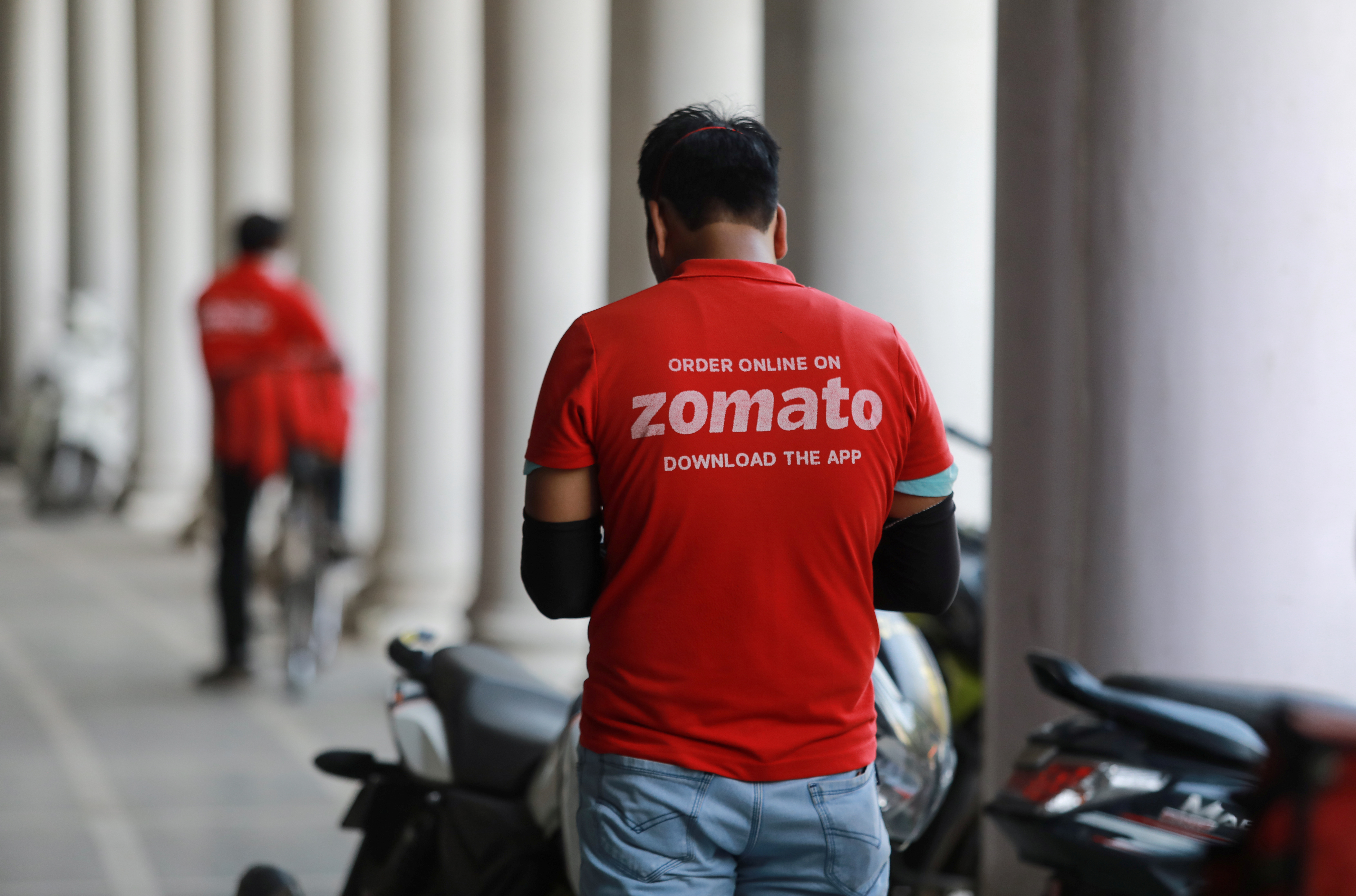 A delivery worker of Zomato, an Indian food-delivery startup, waits to collect an order from a restaurant, during an extended nationwide lockdown to slow the spread of the coronavirus disease (COVID-19), in New Delhi, India, May 21, 2020. REUTERS/Anushree Fadnavis/File Photo
