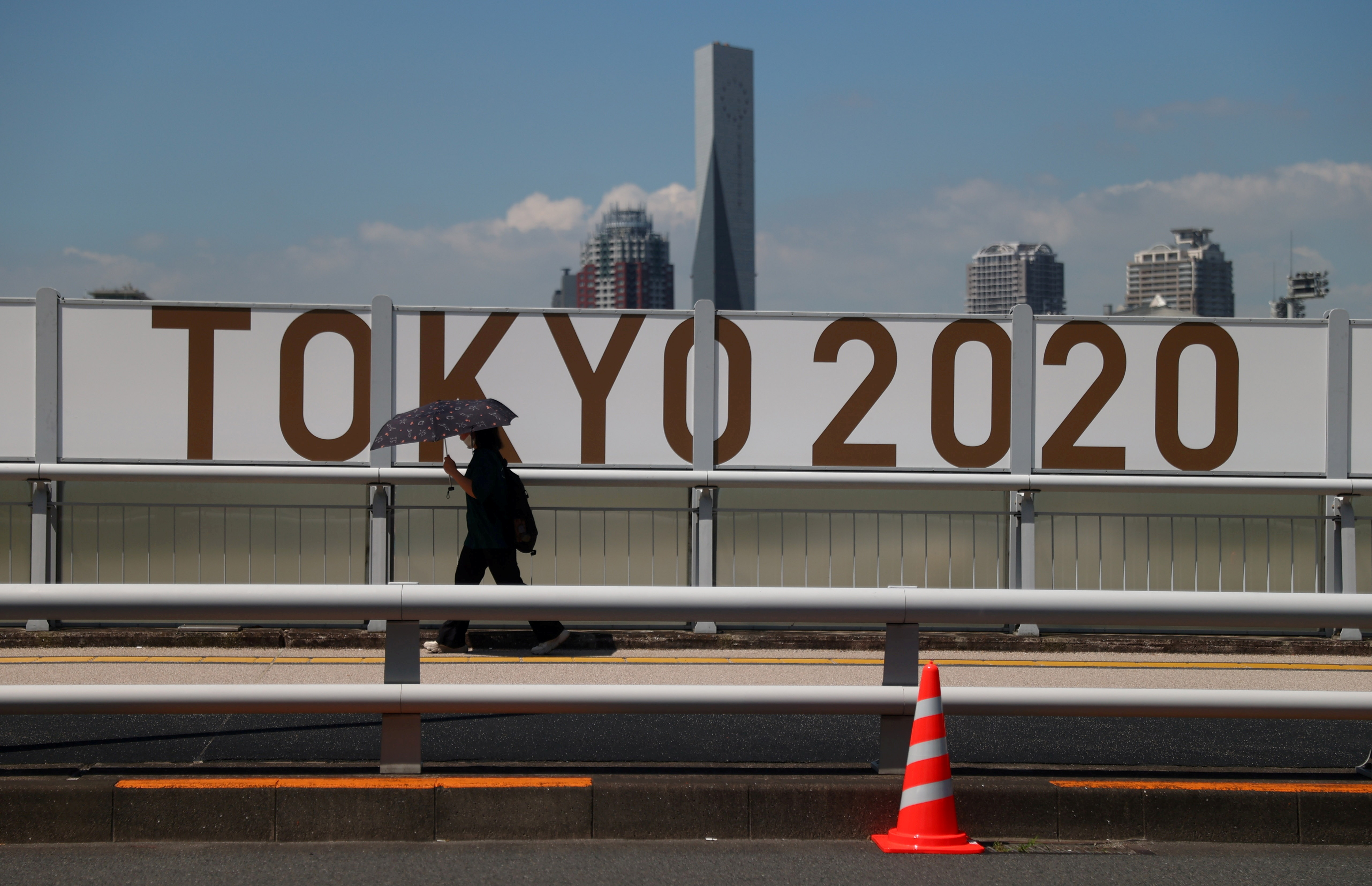 Tokyo 2020 Olympics Preview - Tokyo, Japan - July 19, 2021 A woman shelters from the sun under an umbrella as she walks past Olympics signage REUTERS/Thomas Peter/File Photo