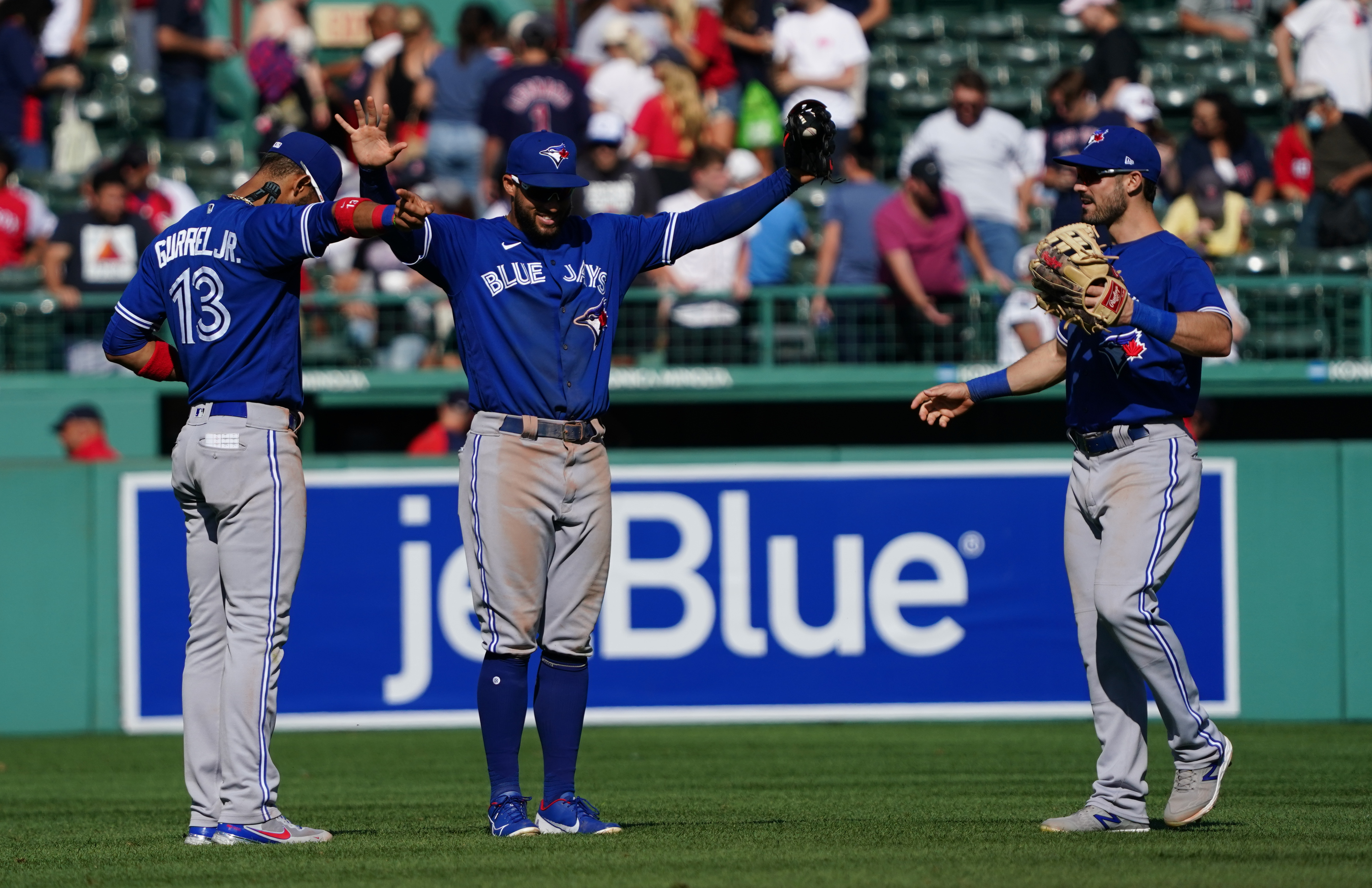 Jul 28, 2021; Boston, Massachusetts, USA; Toronto Blue Jays left fielder Lourdes Gurriel Jr. (13) and center fielder George Springer (4) and right fielder Randal Grichuk (15) celebrate after defeating the Boston Red Sox in the seventh inning of a double header at Fenway Park. Mandatory Credit: David Butler II-USA TODAY Sports