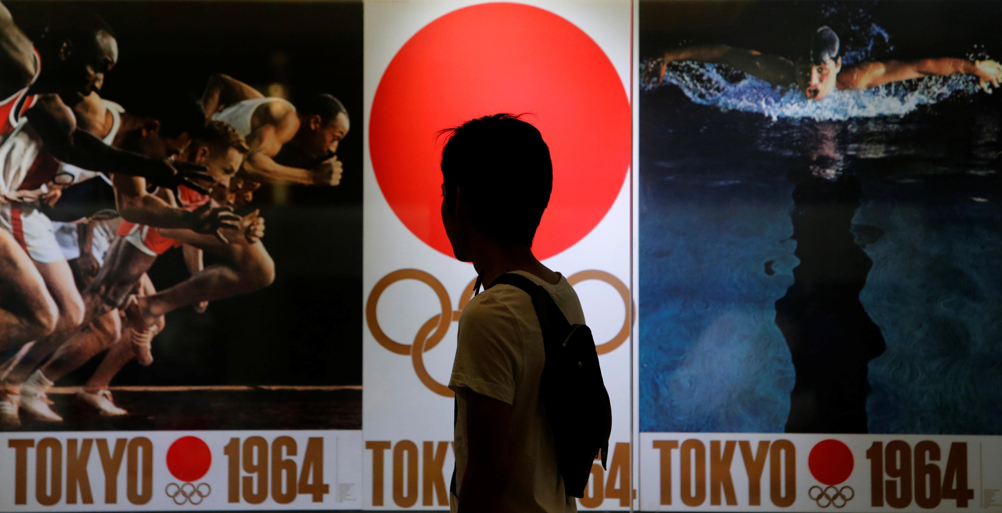 Một người đi bộ xem các bức ảnh của Thế vận hội Mùa hè 1964 ở Tokyo, một phần của triển lãm ảnh bên trong tòa nhà ga xe lửa Tokyo ngày 8 tháng 9 năm 2013. REUTERS / Yuya Shino / File Photo