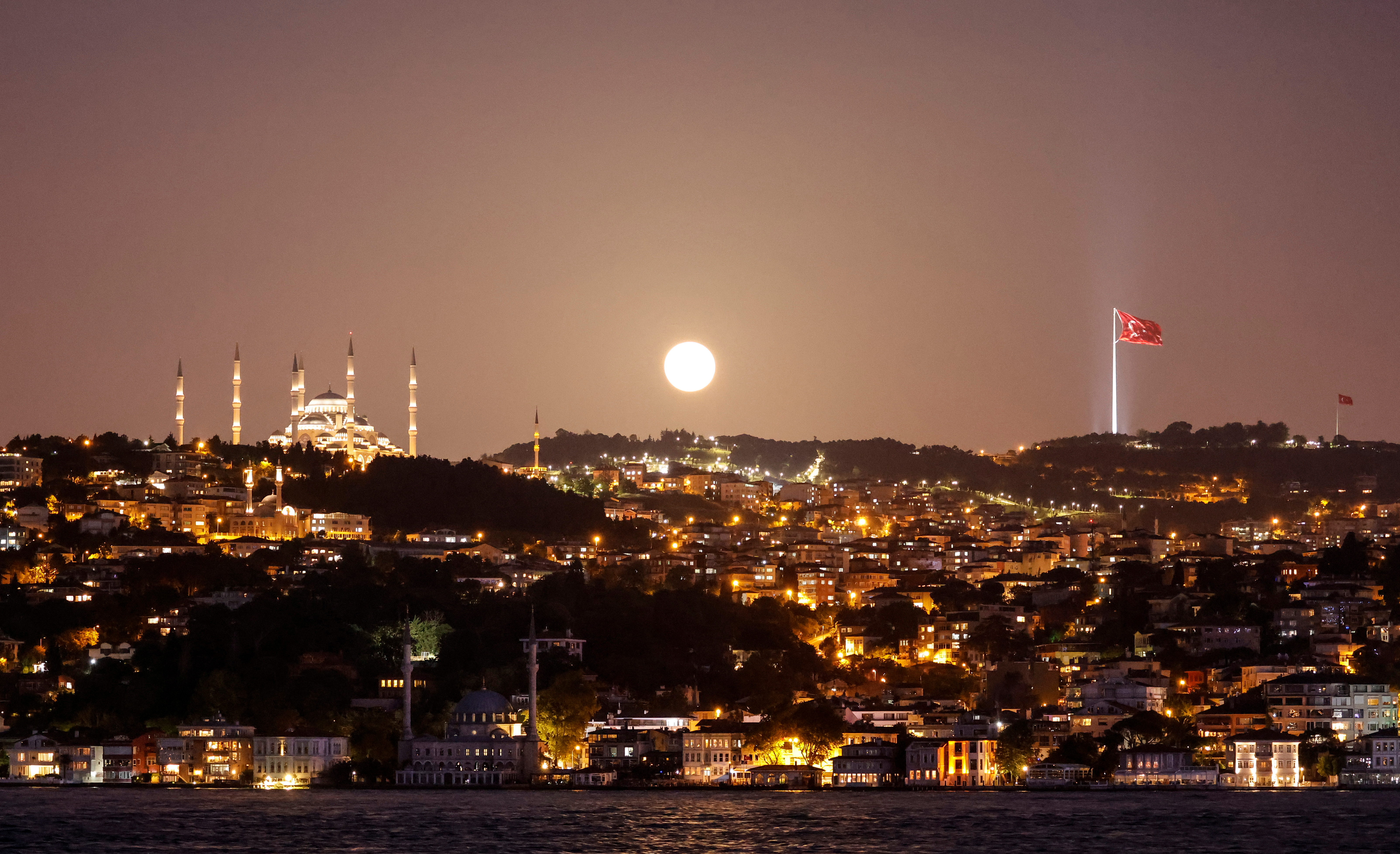 """The full moon, known as the """"Super Flower Moon"""", rises above the Camlica Mosque in Istanbul, Turkey May 26, 2021. REUTERS/Umit Bektas"""