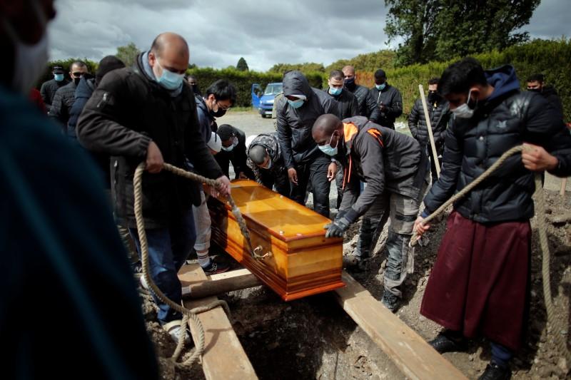 Волонтери на здружението Тахара го погребаа ковчегот на 38-годишниот Абукар Абдулахи Каби, муслимански бегалец, кој почина од коронавирусна болест (КОВИД-19), за време на погребната церемонија на гробиштата во Ла Курнев, во близина на Париз, Франција, мај 17, 2021. Сликана на 17 година. РЕУТЕРС / Беноа Тесие
