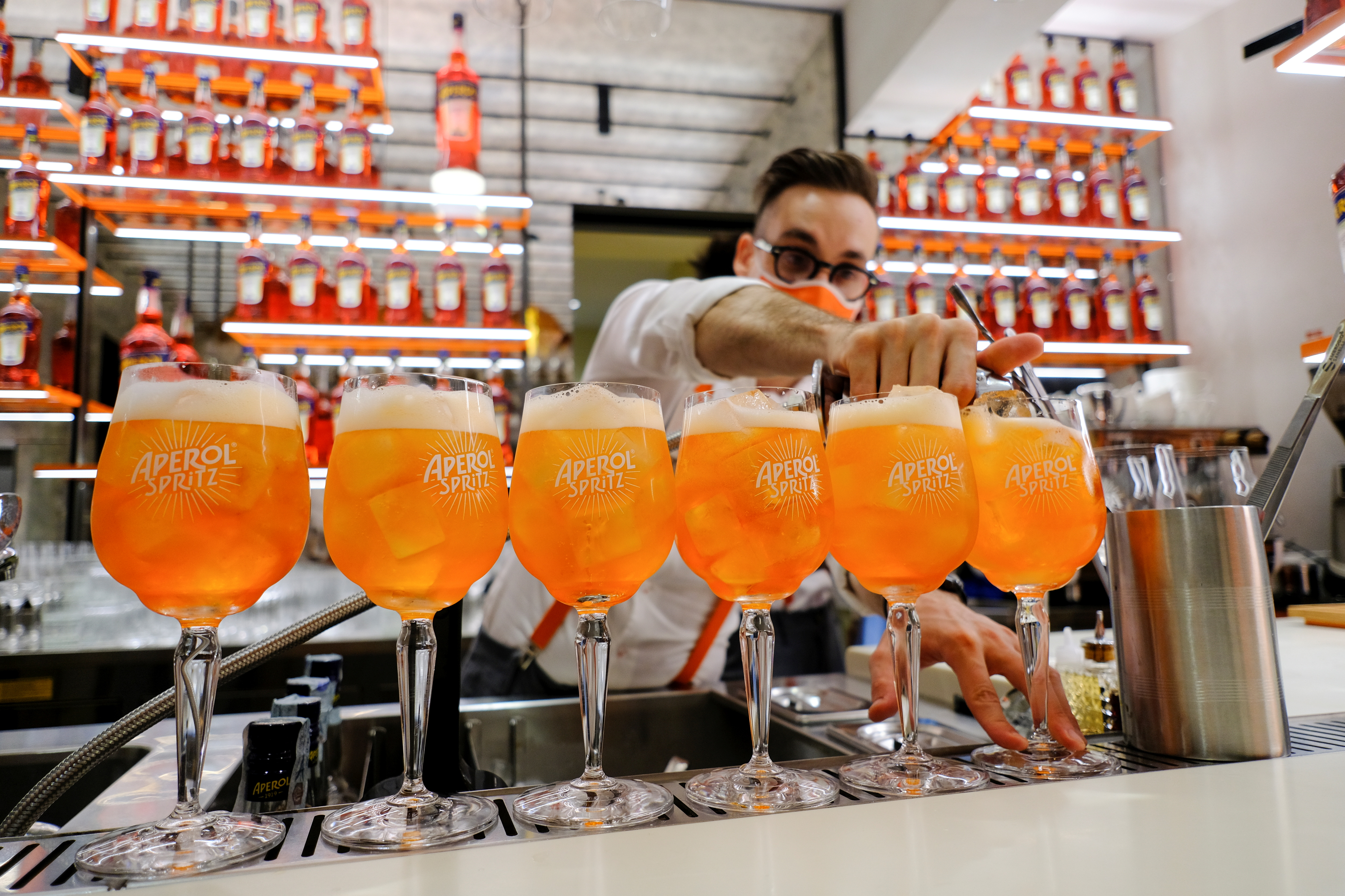 A bartender pours a drink at a Campari inauguration of a new brand house for Aperol, its best-selling beverage, in Venice. Italy, August 30, 2021. REUTERS/Manuel Silvestri
