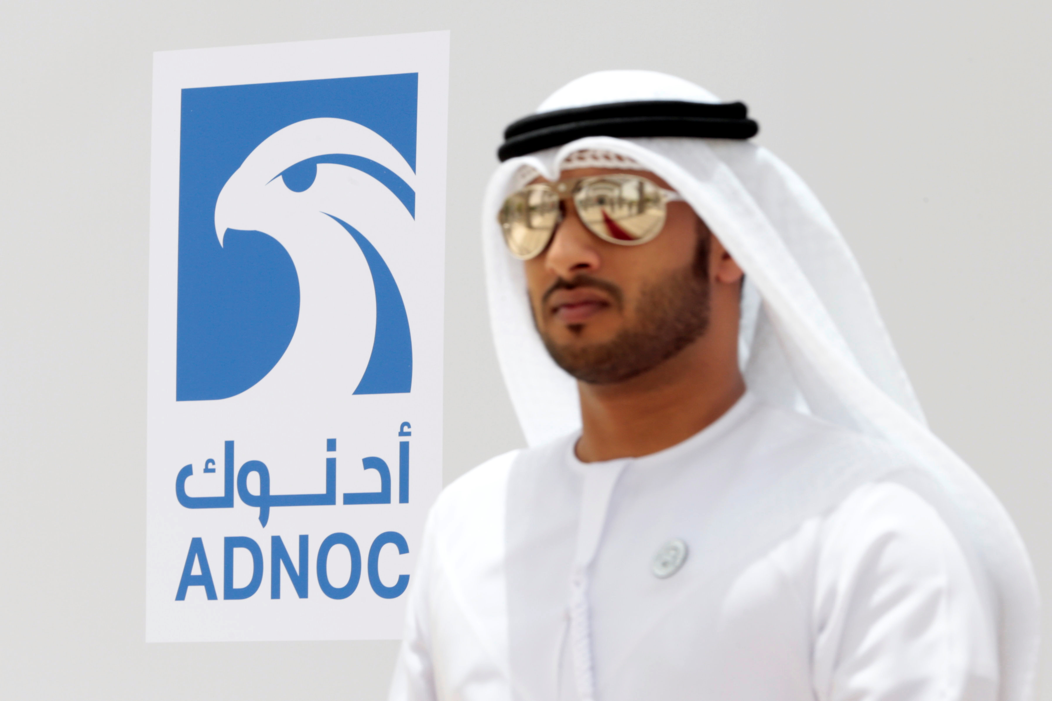 An Emirati man is seen near the logo of  ADNOC in Ruwais, United Arab Emirates May 14, 2018. Picture taken May 14, 2018.REUTERS/Christopher Pike