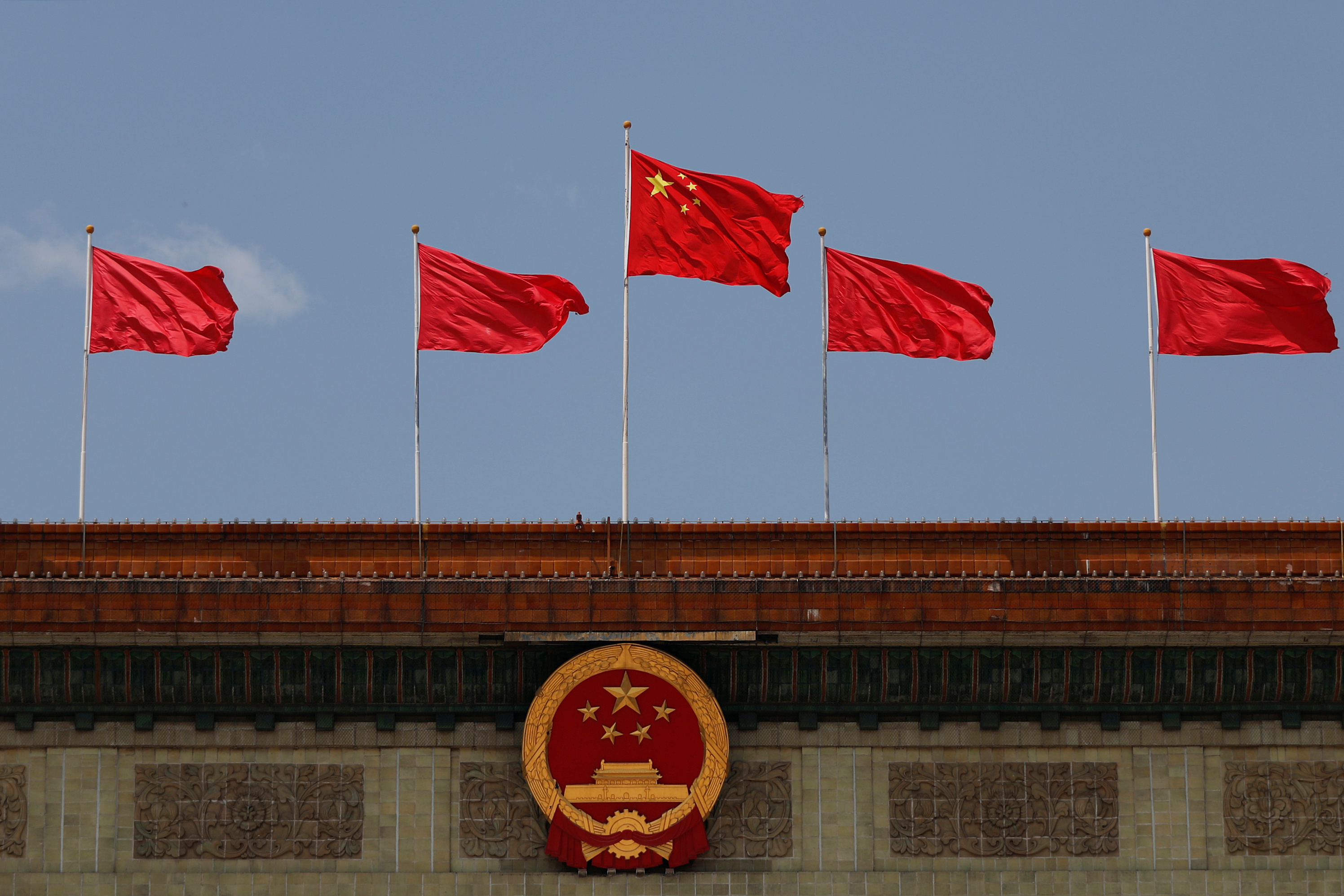 A Chinese flag flutters above the Chinese national emblem at the Great Hall of the People after the opening session of the National People's Congress (NPC) in Beijing, China May 22, 2020. REUTERS/Carlos Garcia Rawlins
