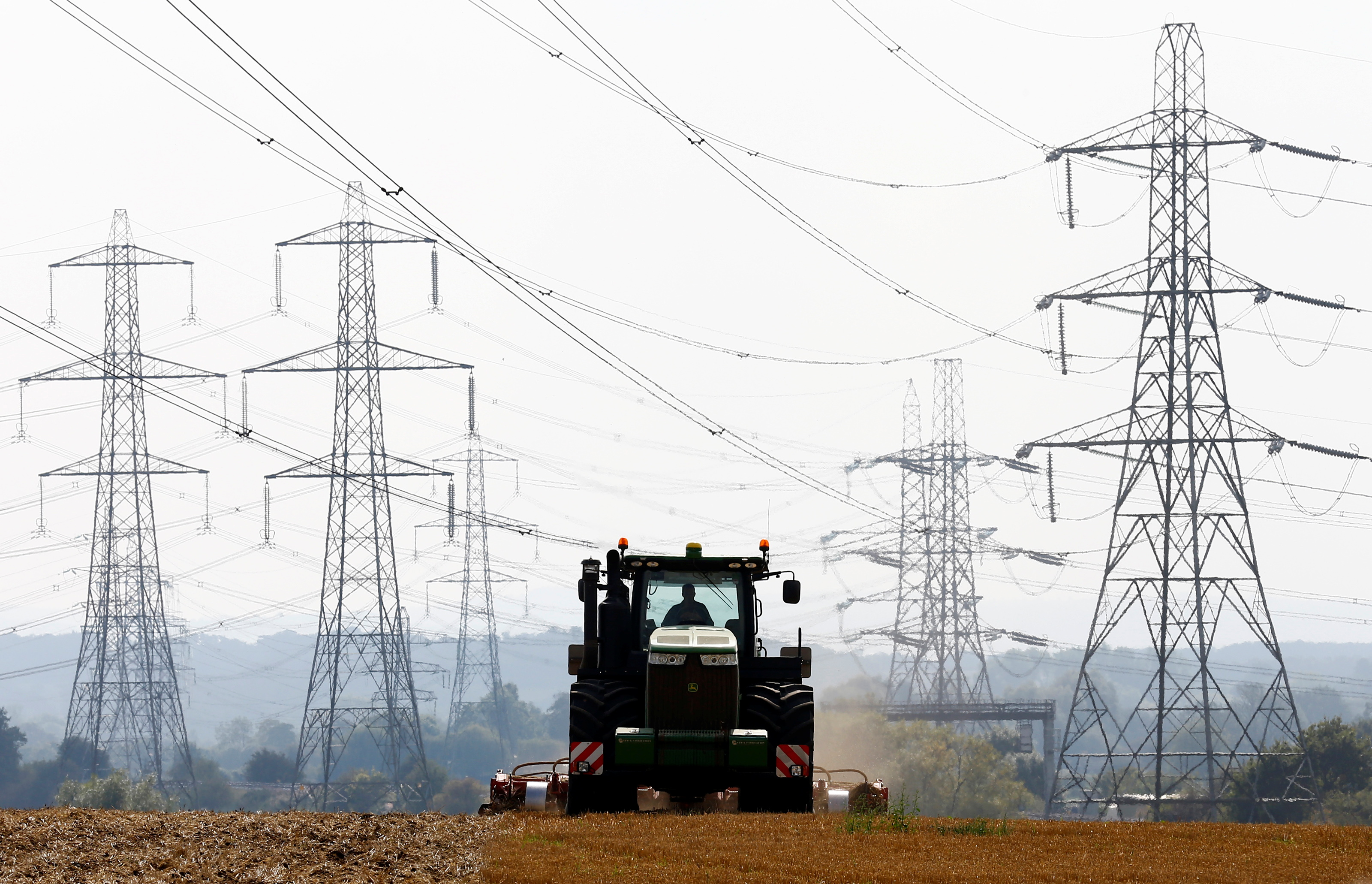 A farmer works in a field surrounded by electricity pylons in Ratcliffe-on-Soar, in central England, September 10, 2014.  REUTERS/Darren Staples/File Photo