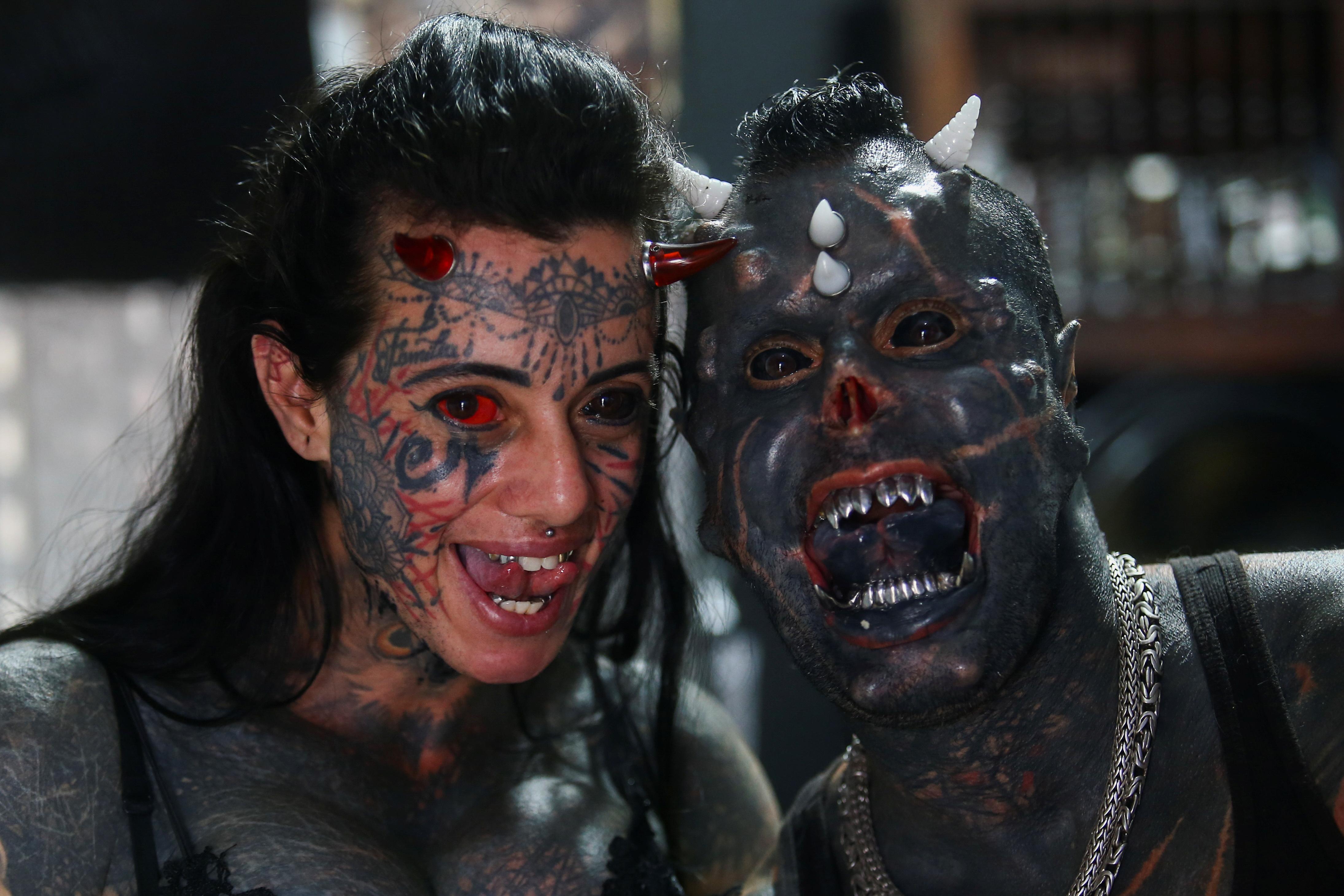 Brazilian tattoo artist Michel Praddo, also known as Diabao or Human Satan, and his wife Carol Praddo, known as Mulher Demonia or Demon Woman, pose in their studio in Praia Grande, Brazil August 18, 2021. REUTERS/Carla Carniel