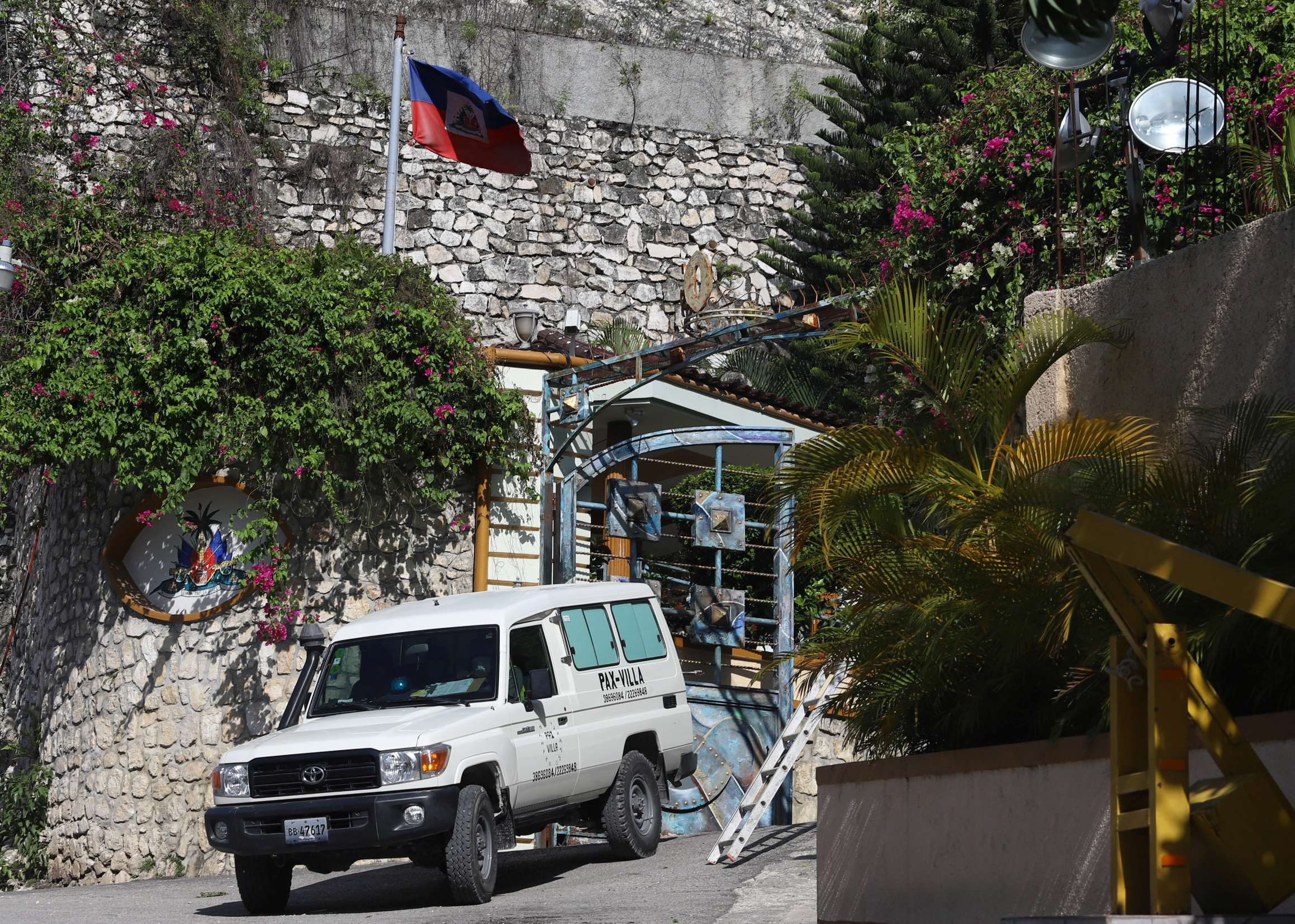 A car from a funeral parlor drives past the coat of arms of Haiti's presidency while leaving the residential area where Haiti's President Jovenel Moise was shot dead at his private home by gunmen with assault rifles, in Port-au-Prince, Haiti July 7, 2021. REUTERS/Estailove St-Val